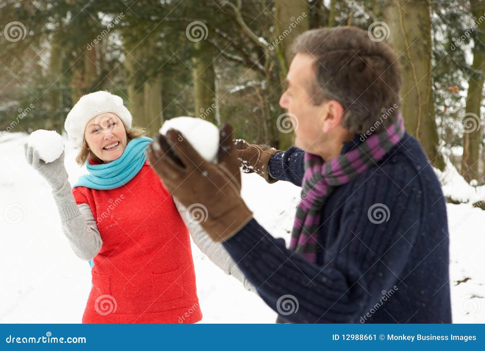 Pares mayores que tienen lucha de la bola de nieve
