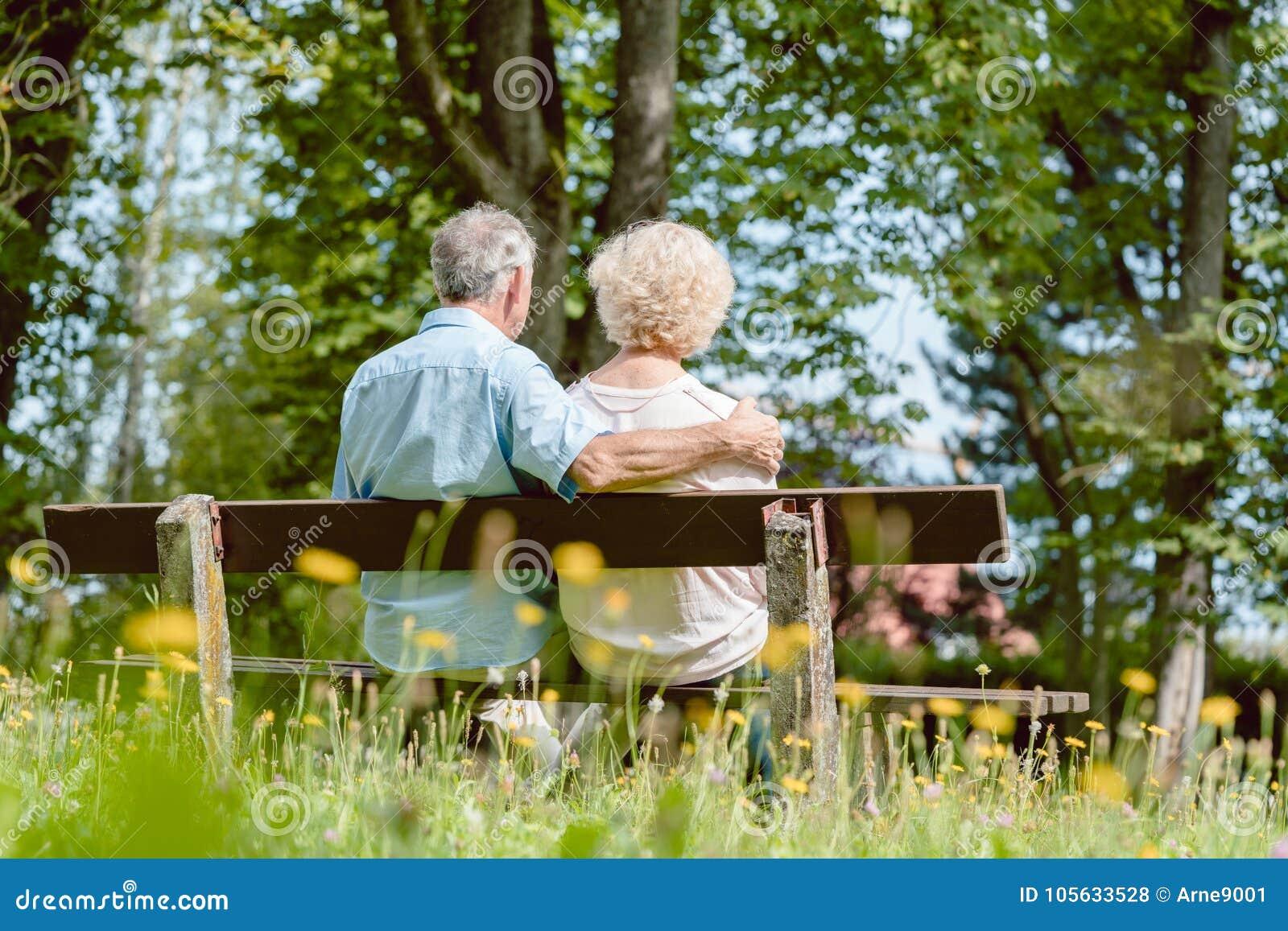 Pares mayores románticos que se sientan junto en un banco en un tranqui