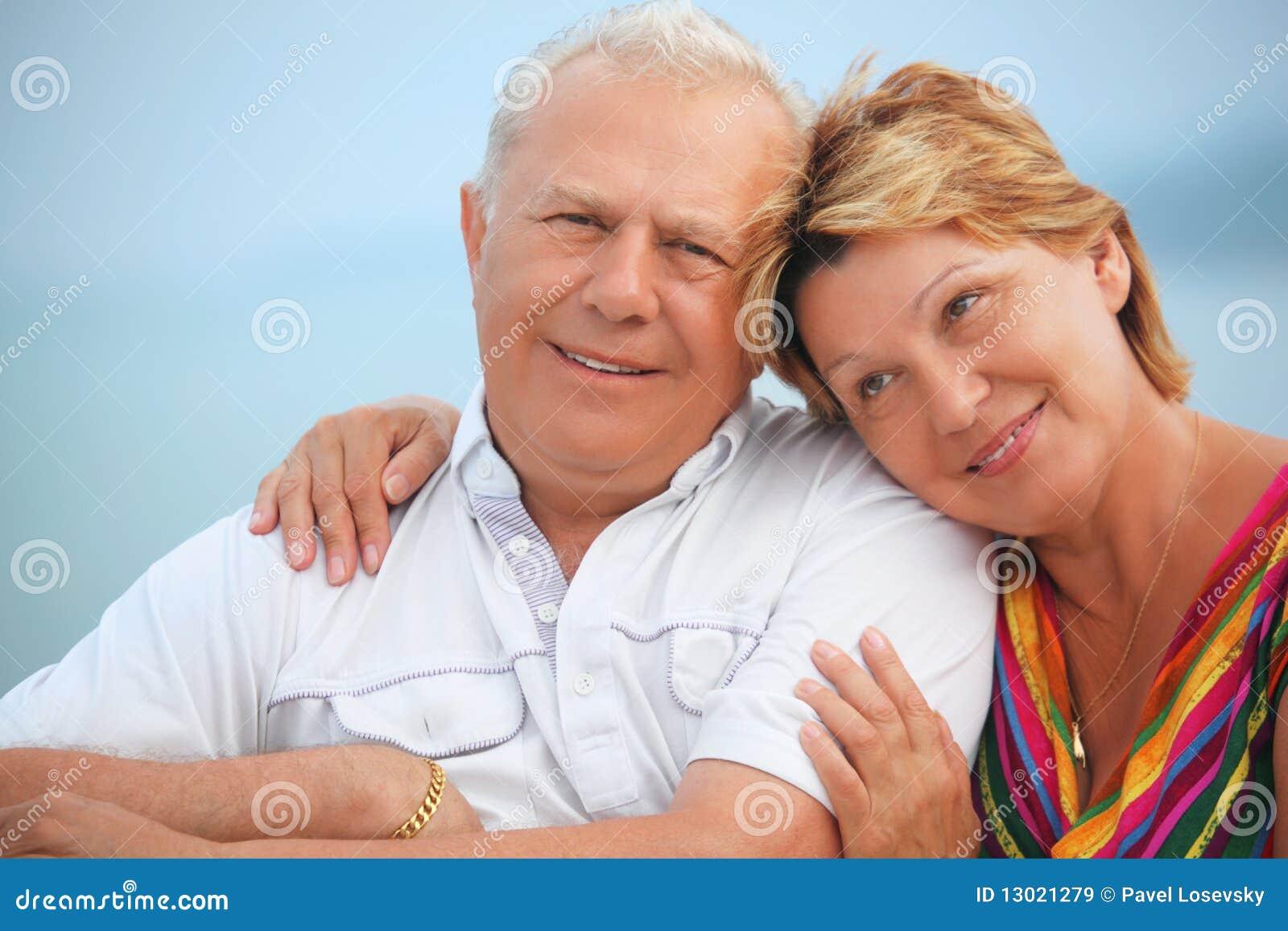 Pares mayores sonrientes en el mirador cerca de la costa