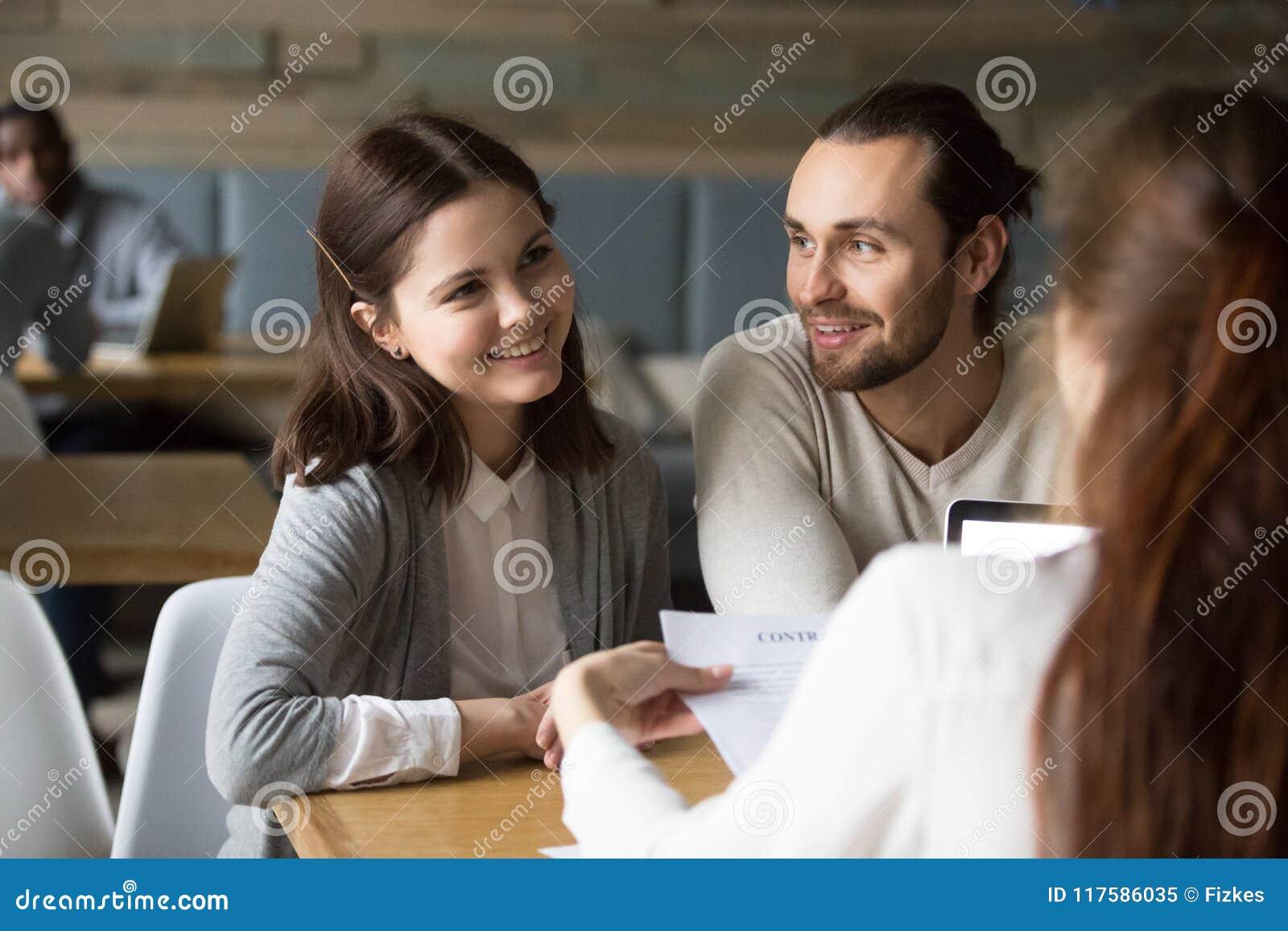 Pares milenares felizes que planeiam assinar o contrato da hipoteca em mim