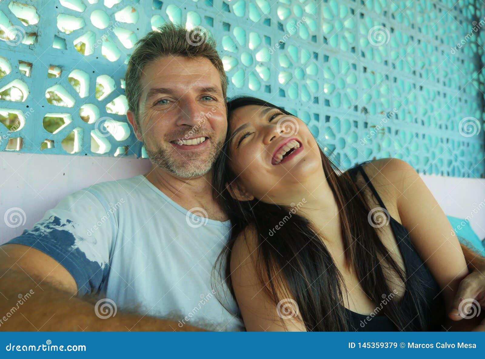 Pares misturados bonitos e felizes novos da afiliação étnica no sorriso do amor alegre junto com o homem caucasiano considerá