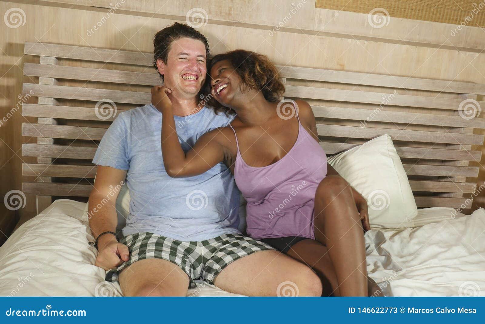 Pares misturados da afilia??o ?tnica no amor que afaga junto em casa na cama com a amiga ou a esposa afro-americana preta brincal