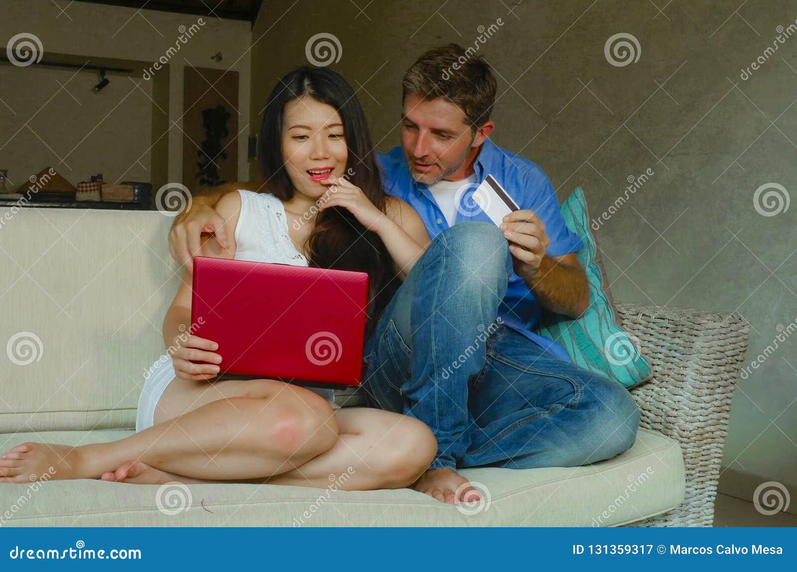 Pares misturados felizes e entusiasmados novos da afiliação étnica com os Internet banking da mulher chinesa asiática e do homem