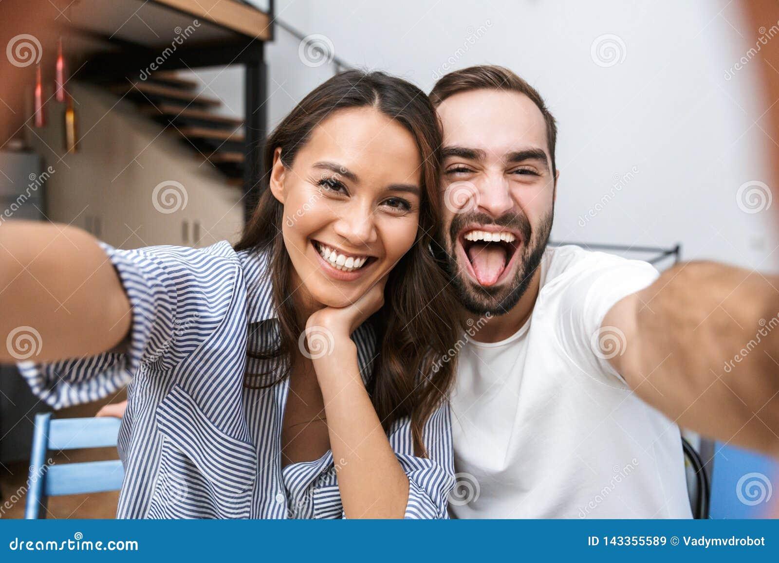 Pares multiétnicos alegres que toman un selfie