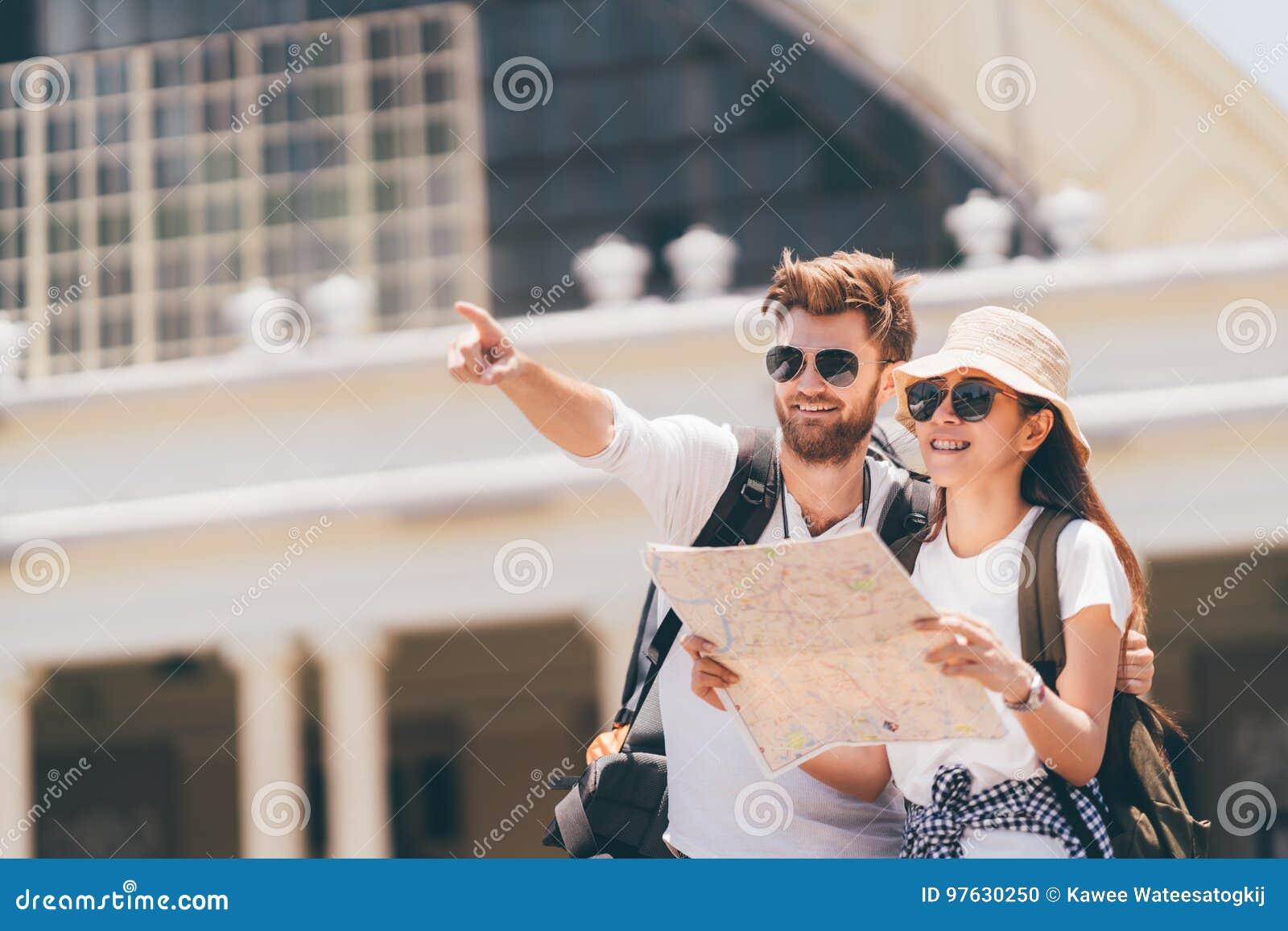 Pares multiétnicos del viajero usando mapa local genérico junto el día soleado Viaje de la luna de miel, turista del backpacker,