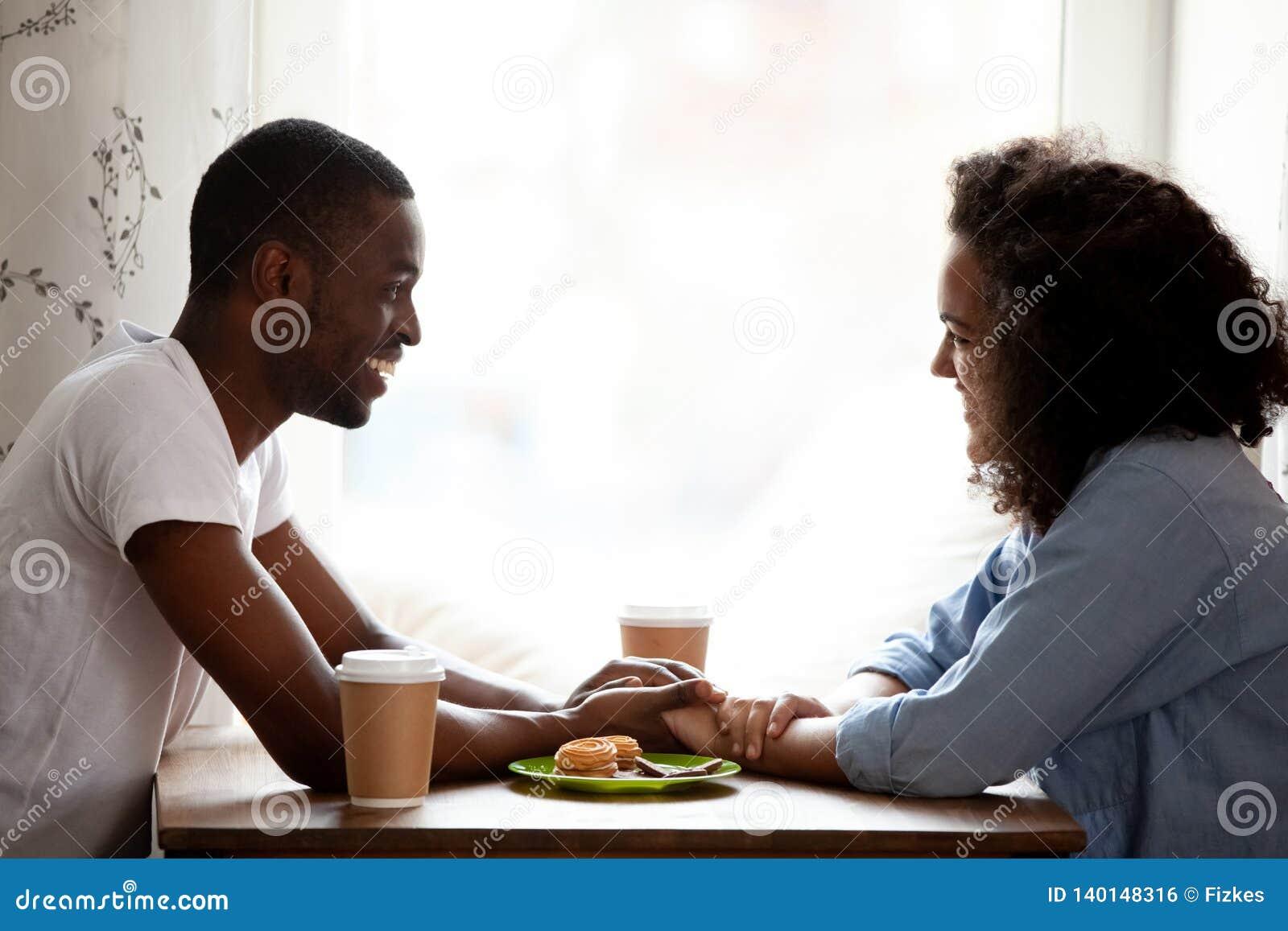 Pares multirraciais felizes que guardam as mãos, apreciando a data no café