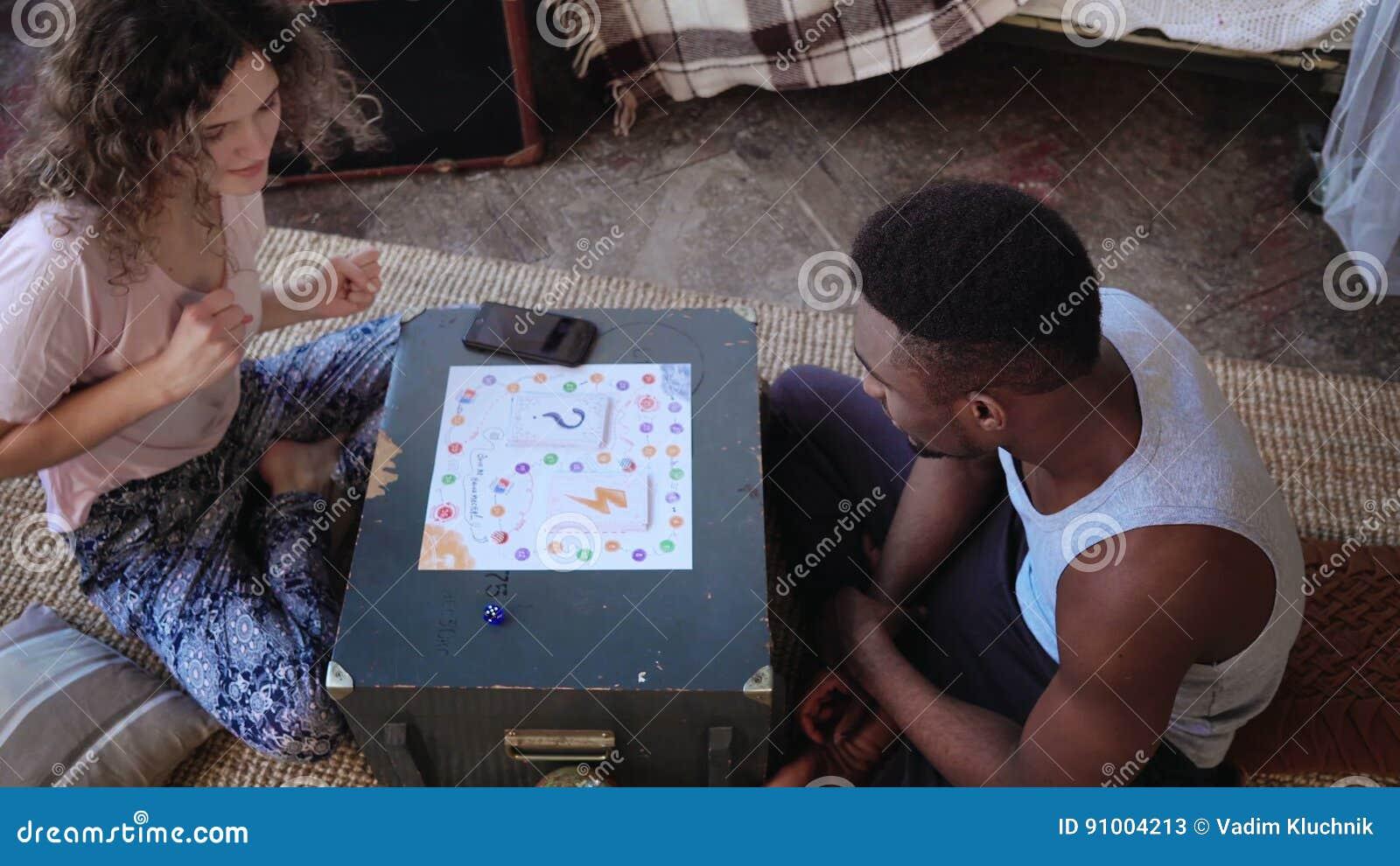 Pares multirraciales, hombre y mujer en los pijamas que juegan al juego de mesa Los tiros de la muchacha cortan en cuadritos y ba
