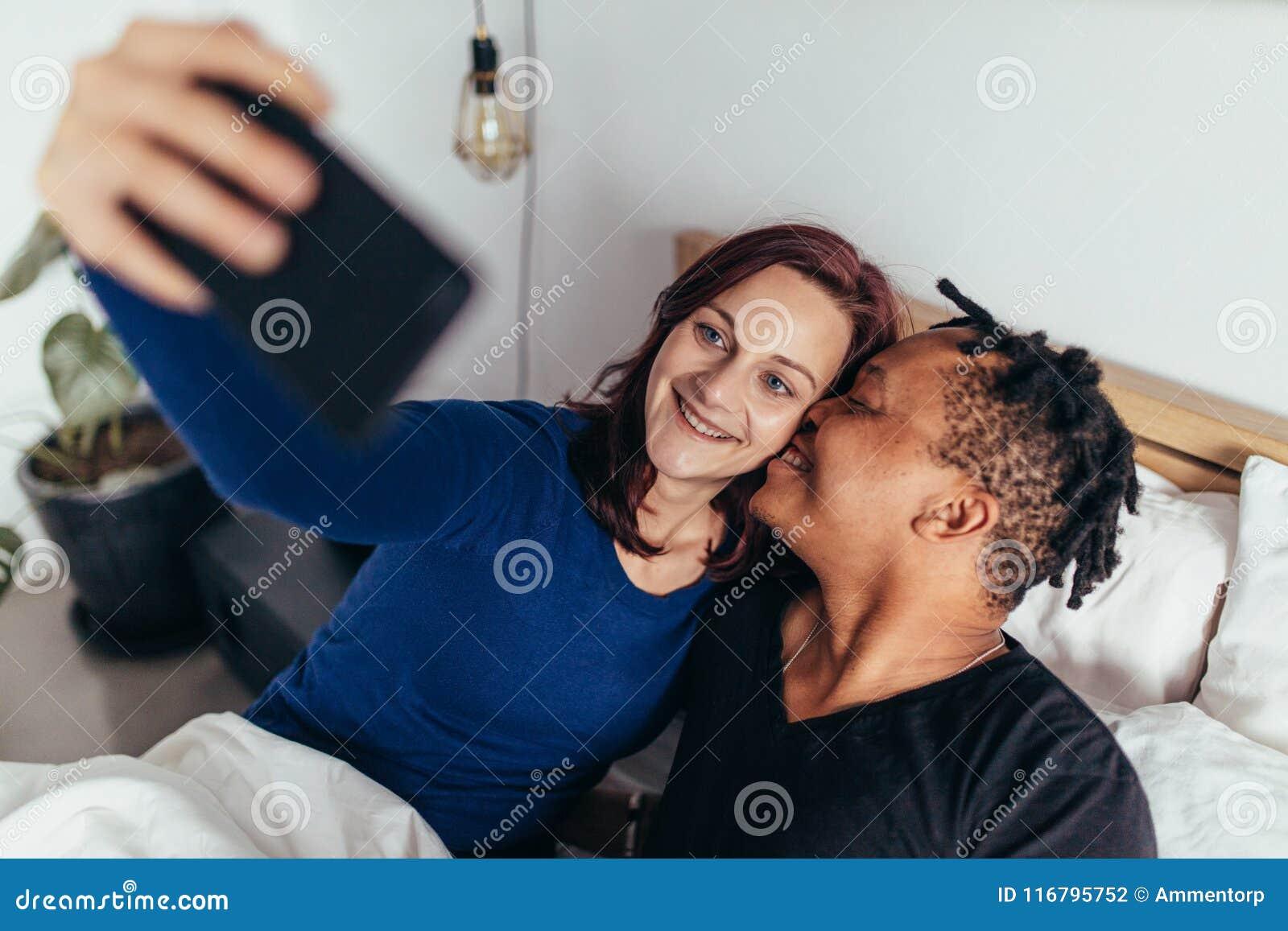 Pares multirraciales románticos que toman el selfie en cama
