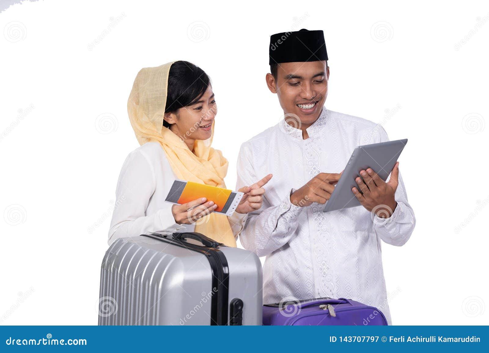 Pares musulmanes usando la PC de la tableta antes de viajar