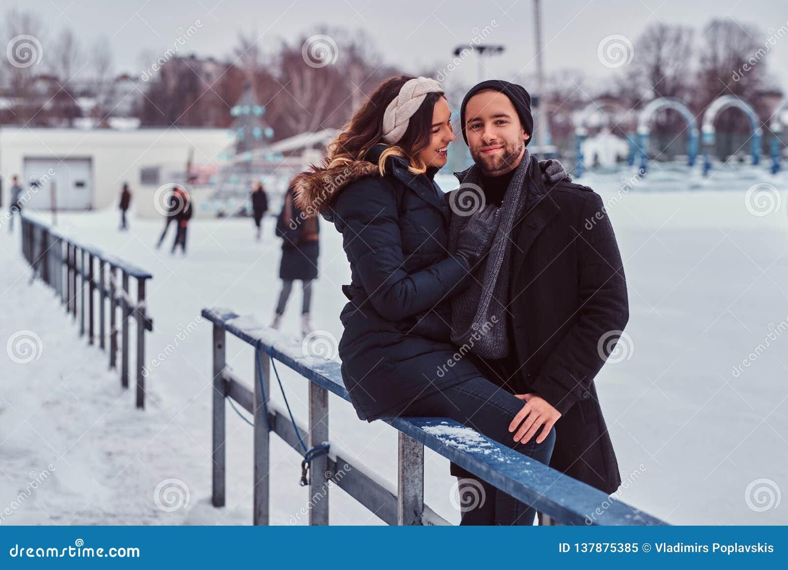 Pares no amor, data na pista de gelo, uma menina que senta-se em um corrimão e que abraça com seu noivo