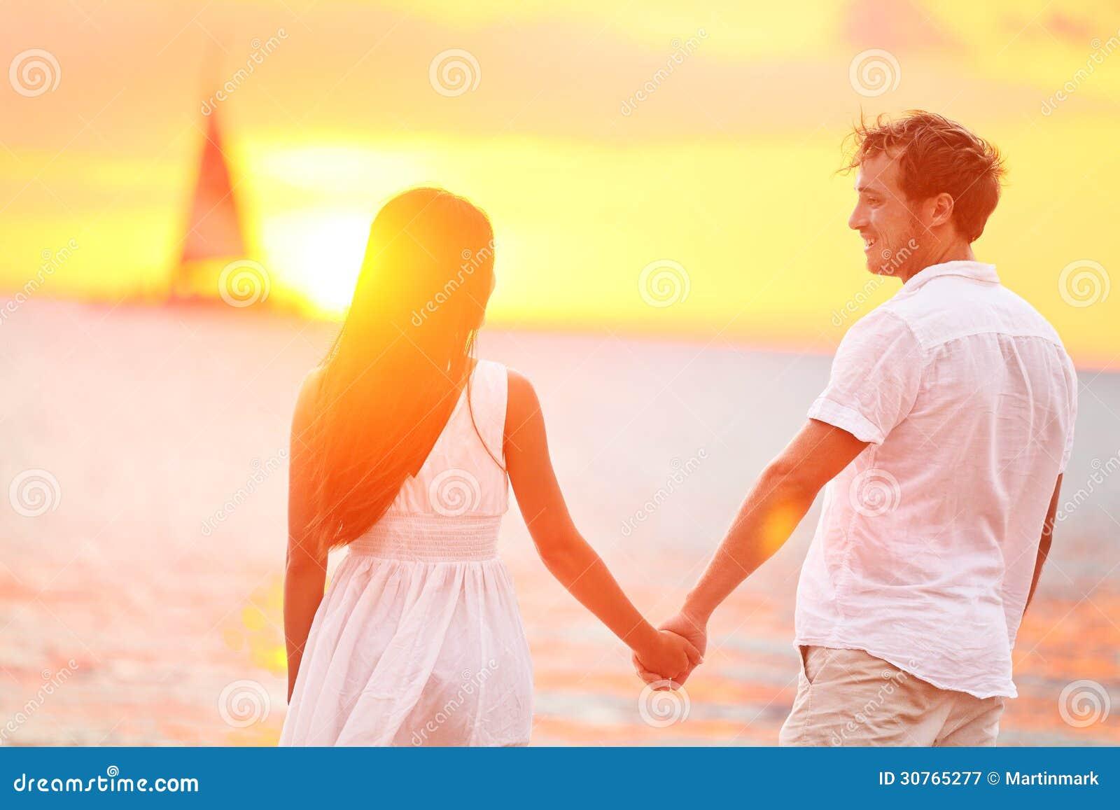 Pares no amor feliz no por do sol romântico da praia