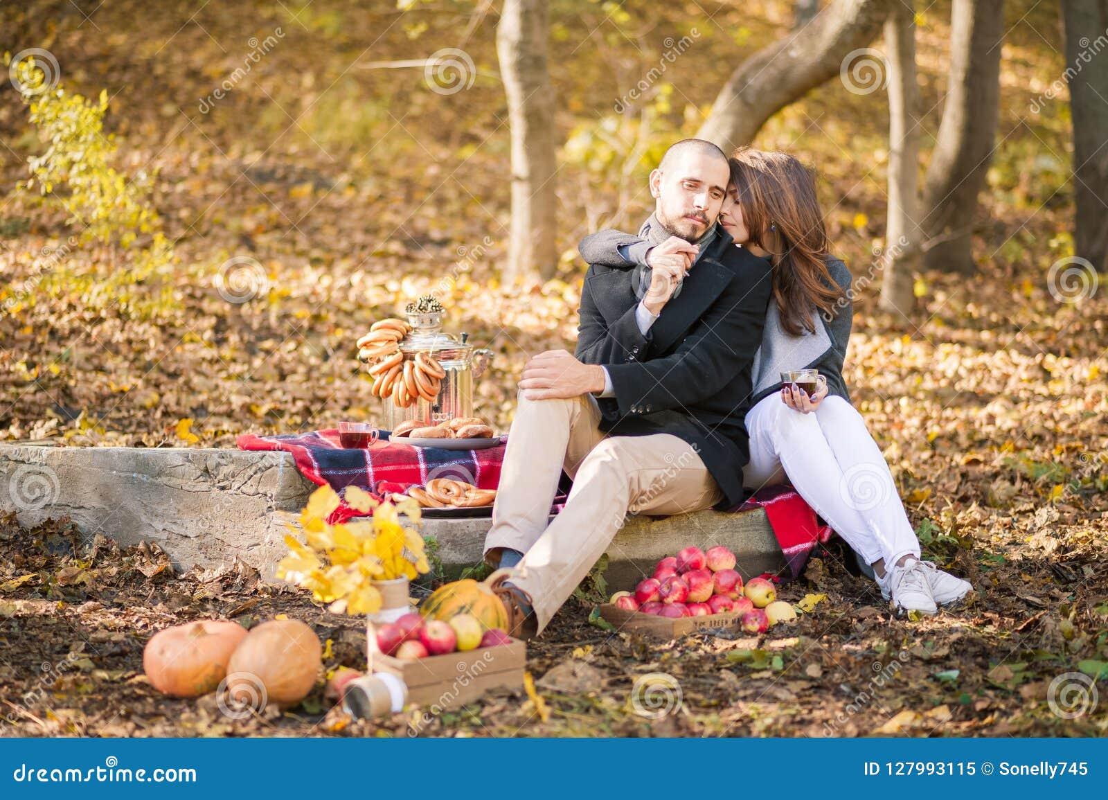 Pares no amor na queda em um piquenique Os amantes estão beijando, abraçar, bebendo a bebida Vapor e abóbora, folhas amarelas, t