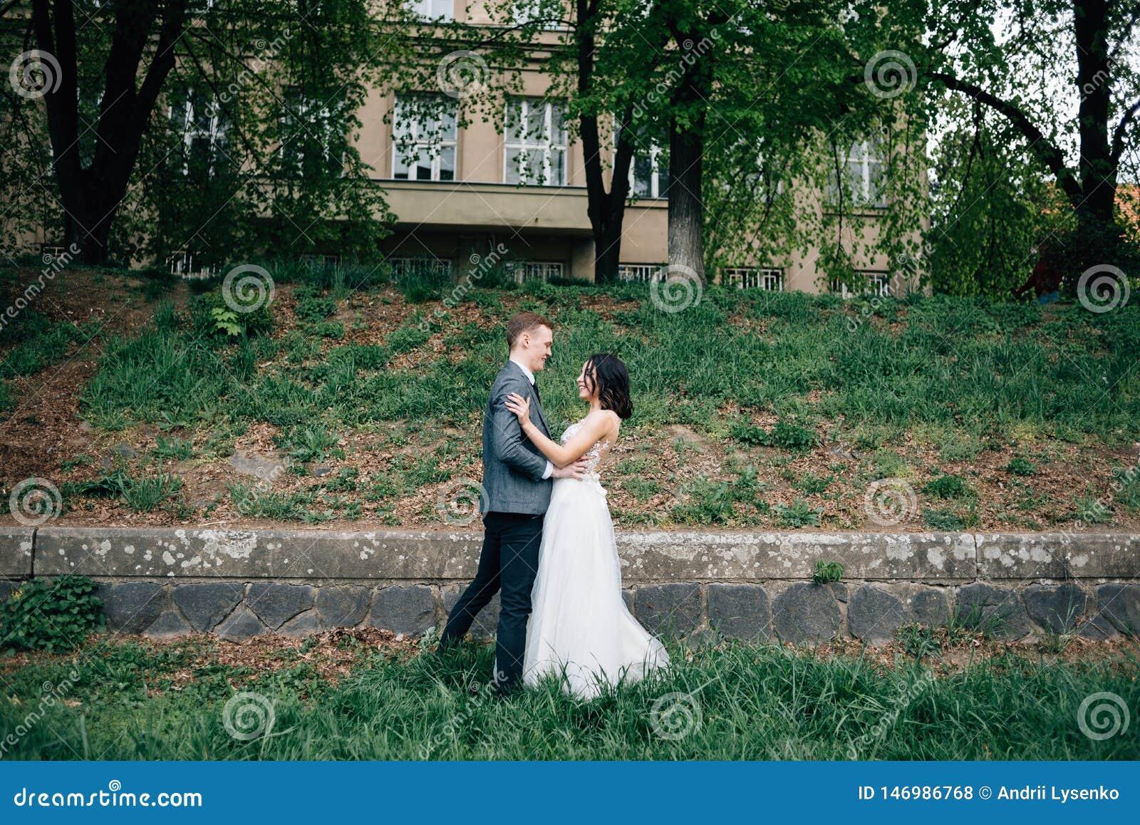 Pares no amor, noivos, caminhada no ar fresco Natureza, grama e árvores verdes