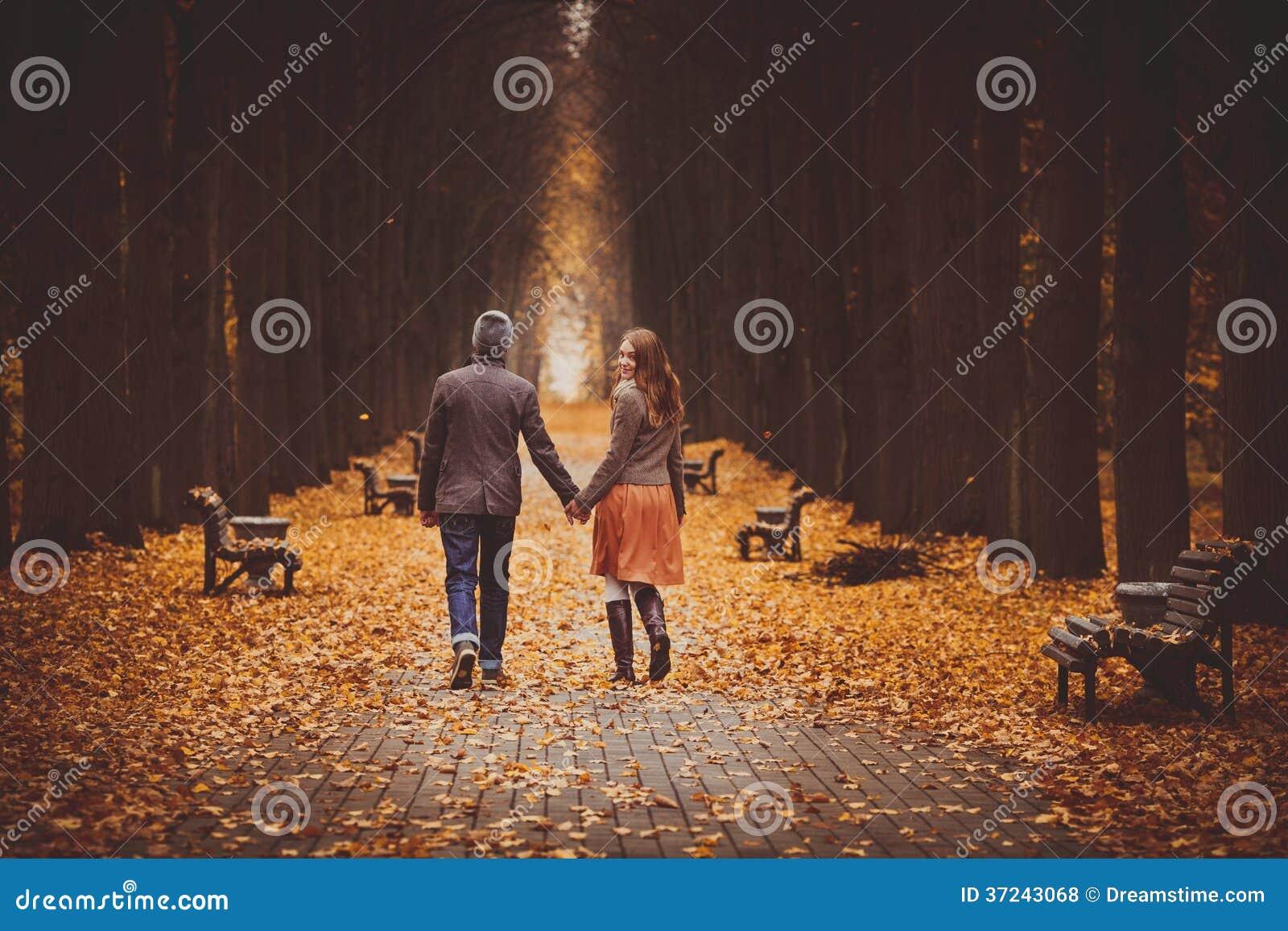 Pares no amor que anda em uma aleia bonita do outono no parque
