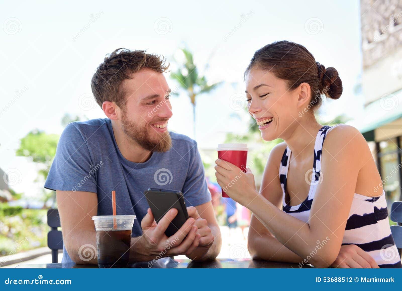 Pares no café que olha imagens espertas do app do telefone