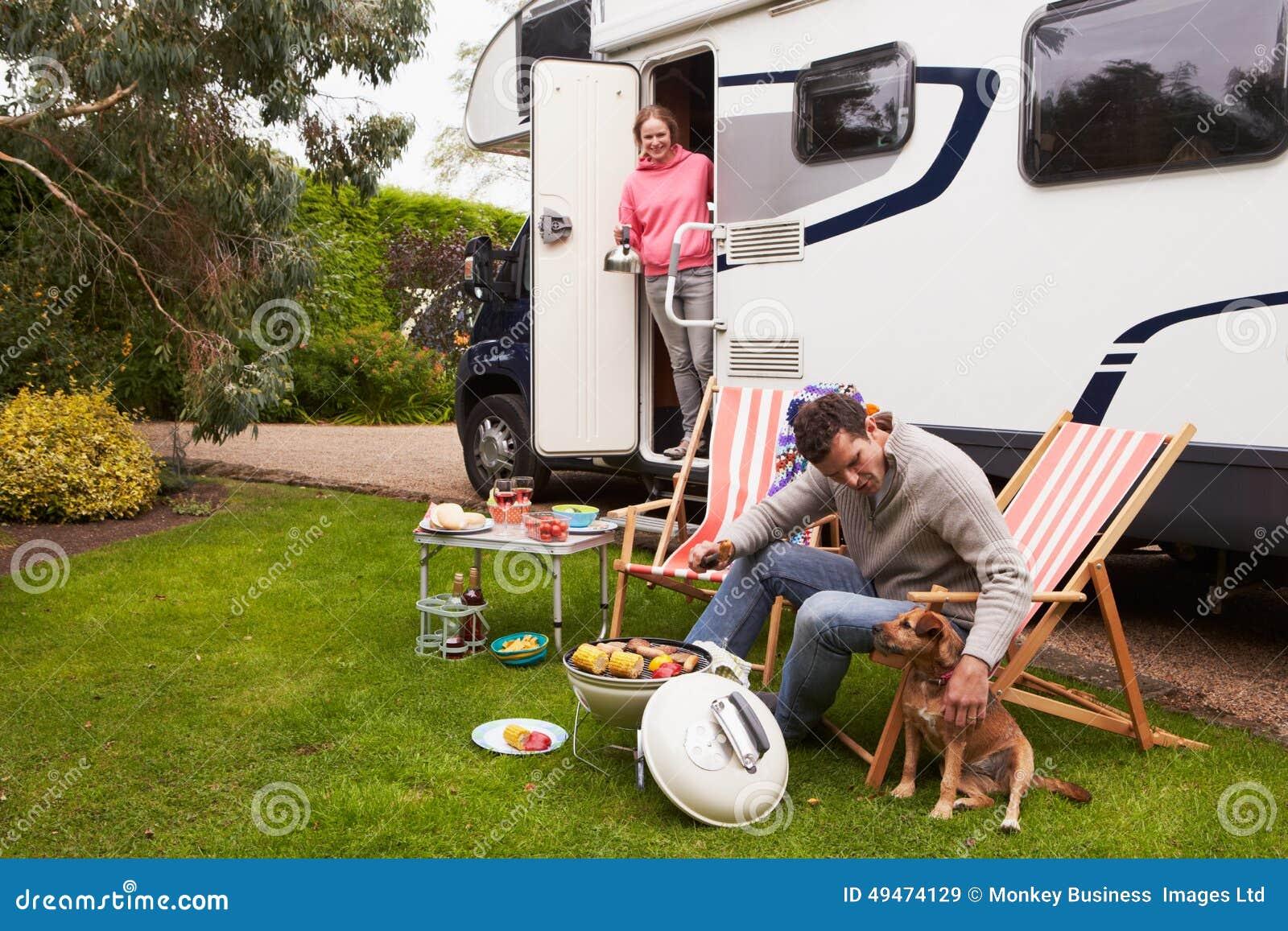 Pares no feriado de Van Enjoying Barbeque On Camping