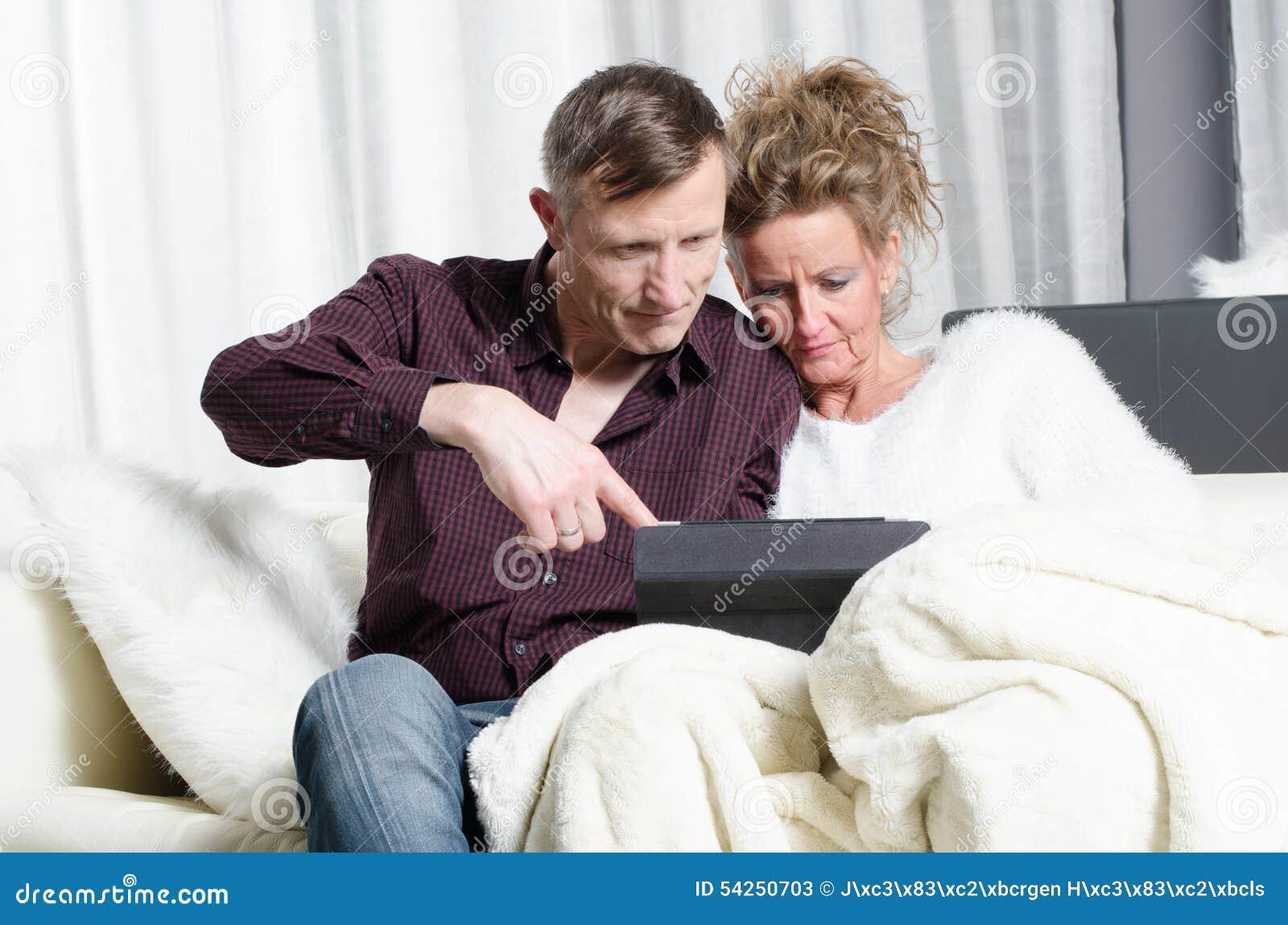 Pares no sofá que olha na tabuleta