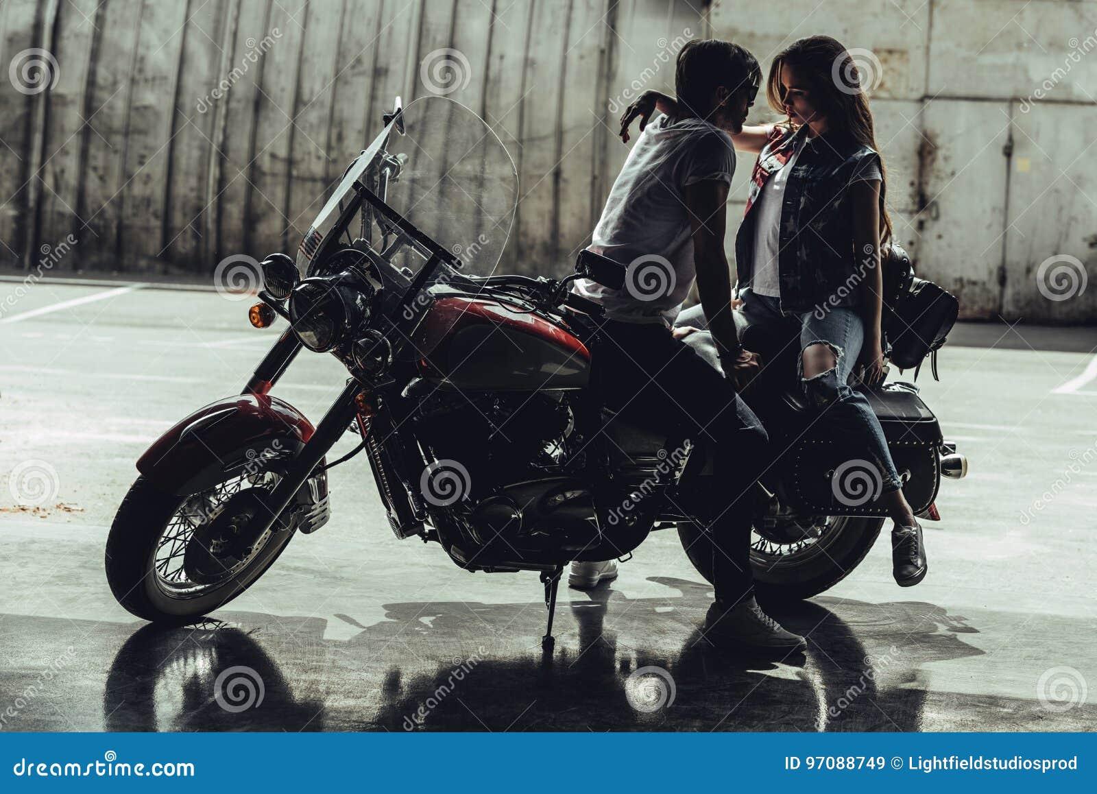 Pares novos à moda que sentam-se na motocicleta e que olham se