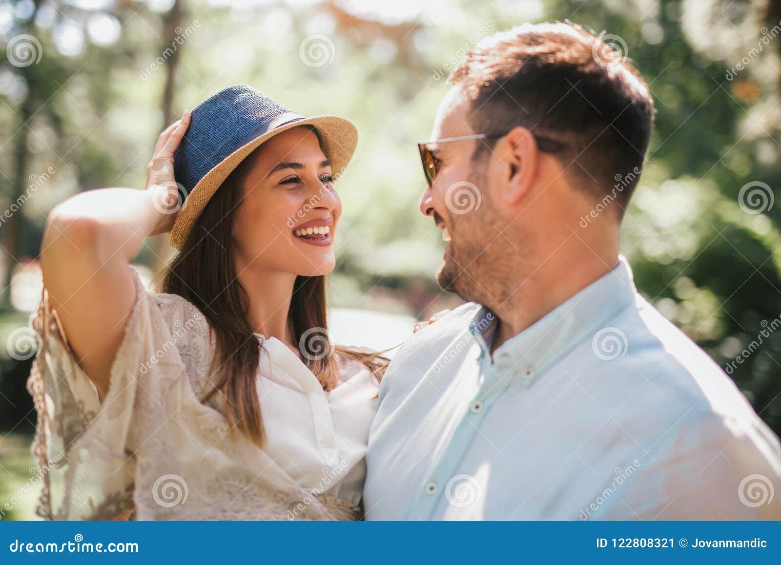Pares novos alegres que têm o divertimento e que riem junto
