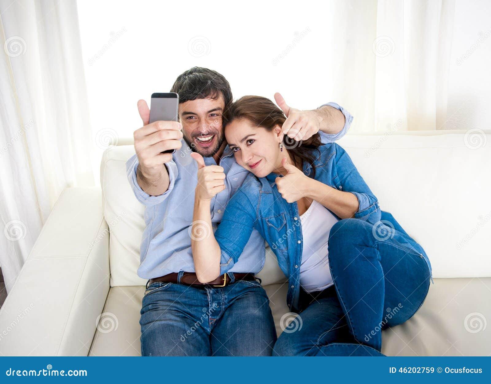 Pares novos atrativos agradáveis que sentam-se junto no sofá do sofá que toma a foto do selfie com telefone celular