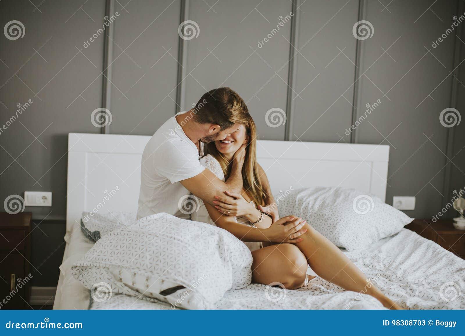 Pares novos bonitos que beijam na cama