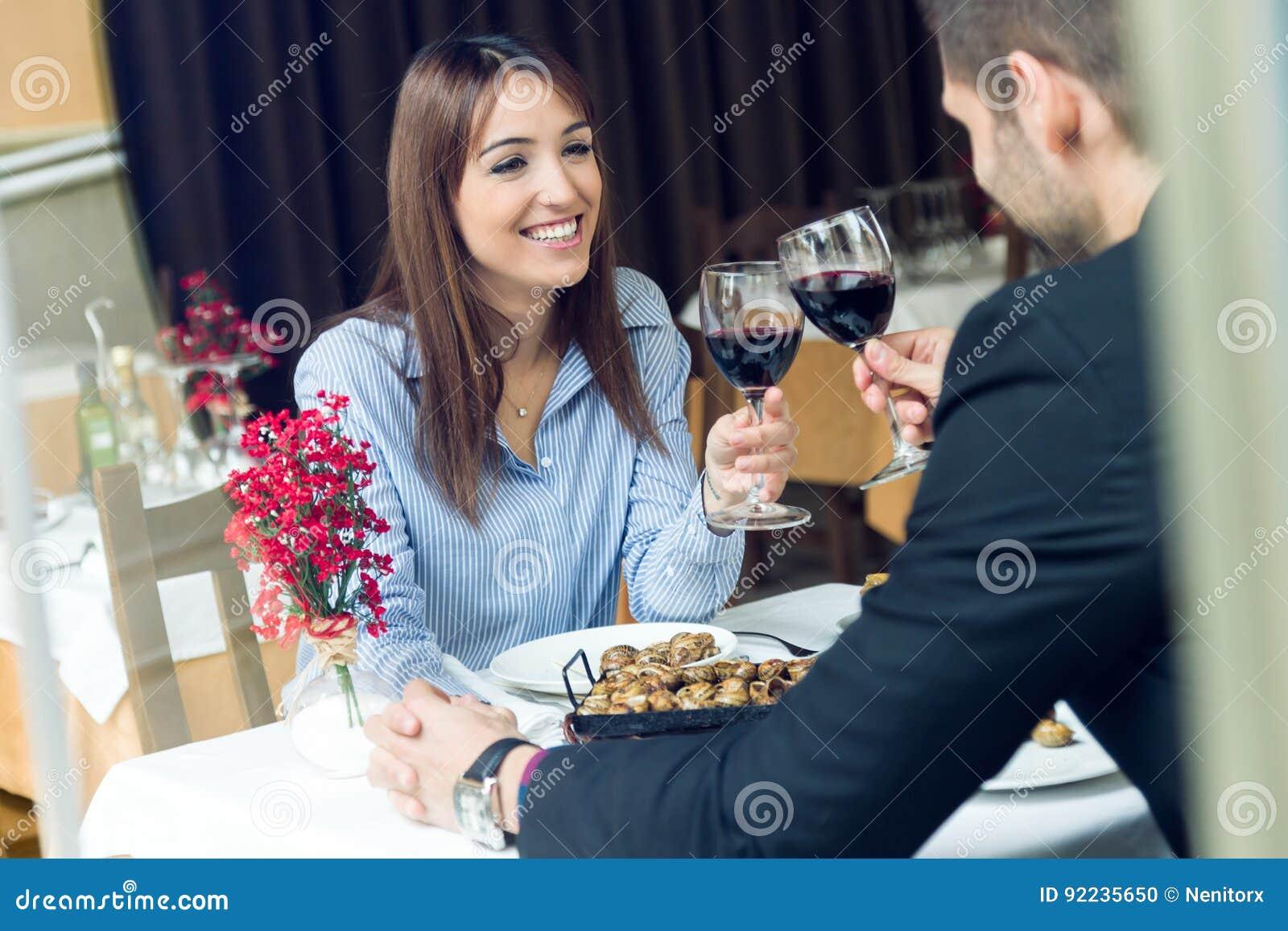 Pares novos bonitos que brindam vidros de vinho no restaurante