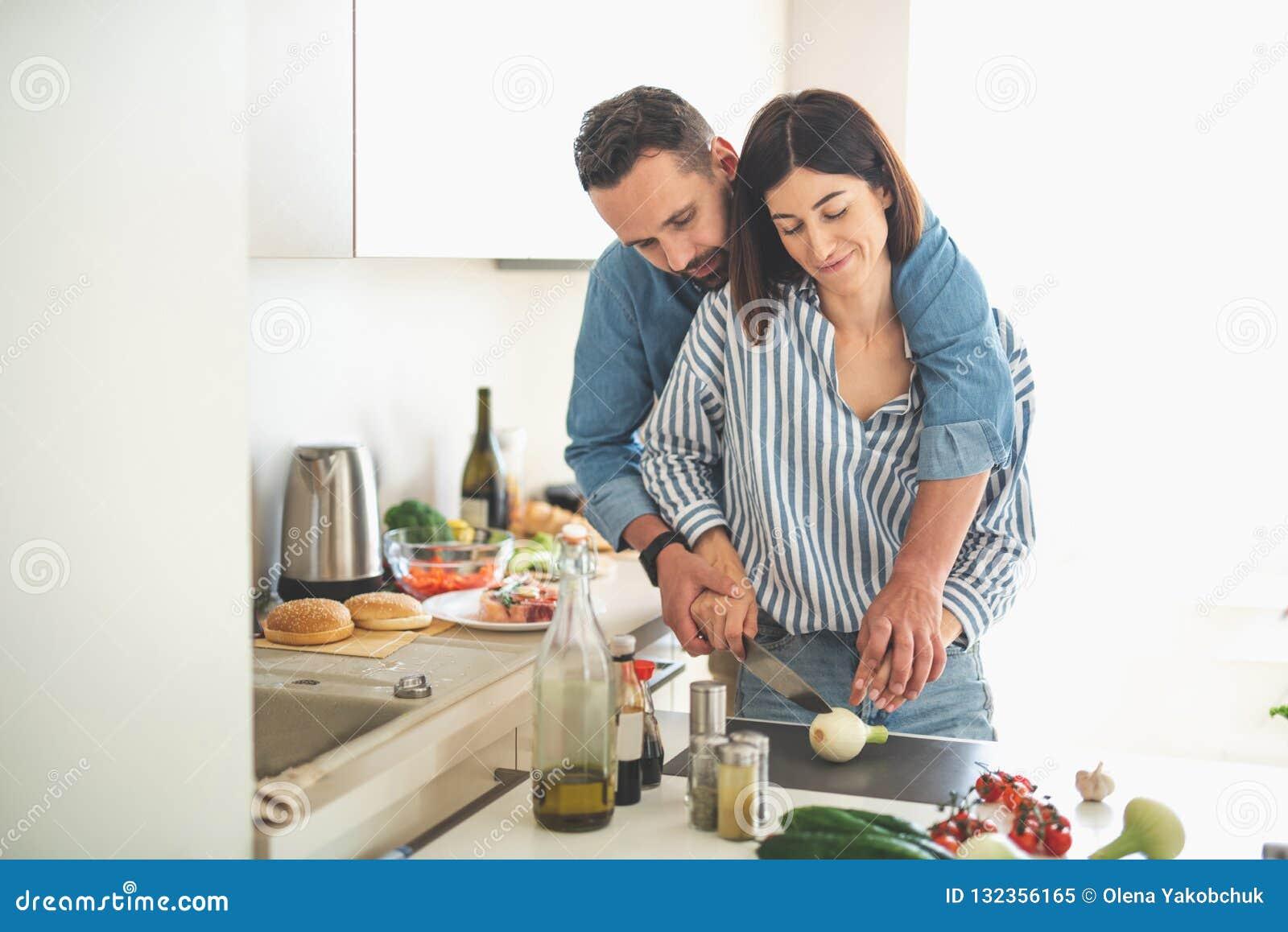 Pares novos bonitos que cozinham junto em casa