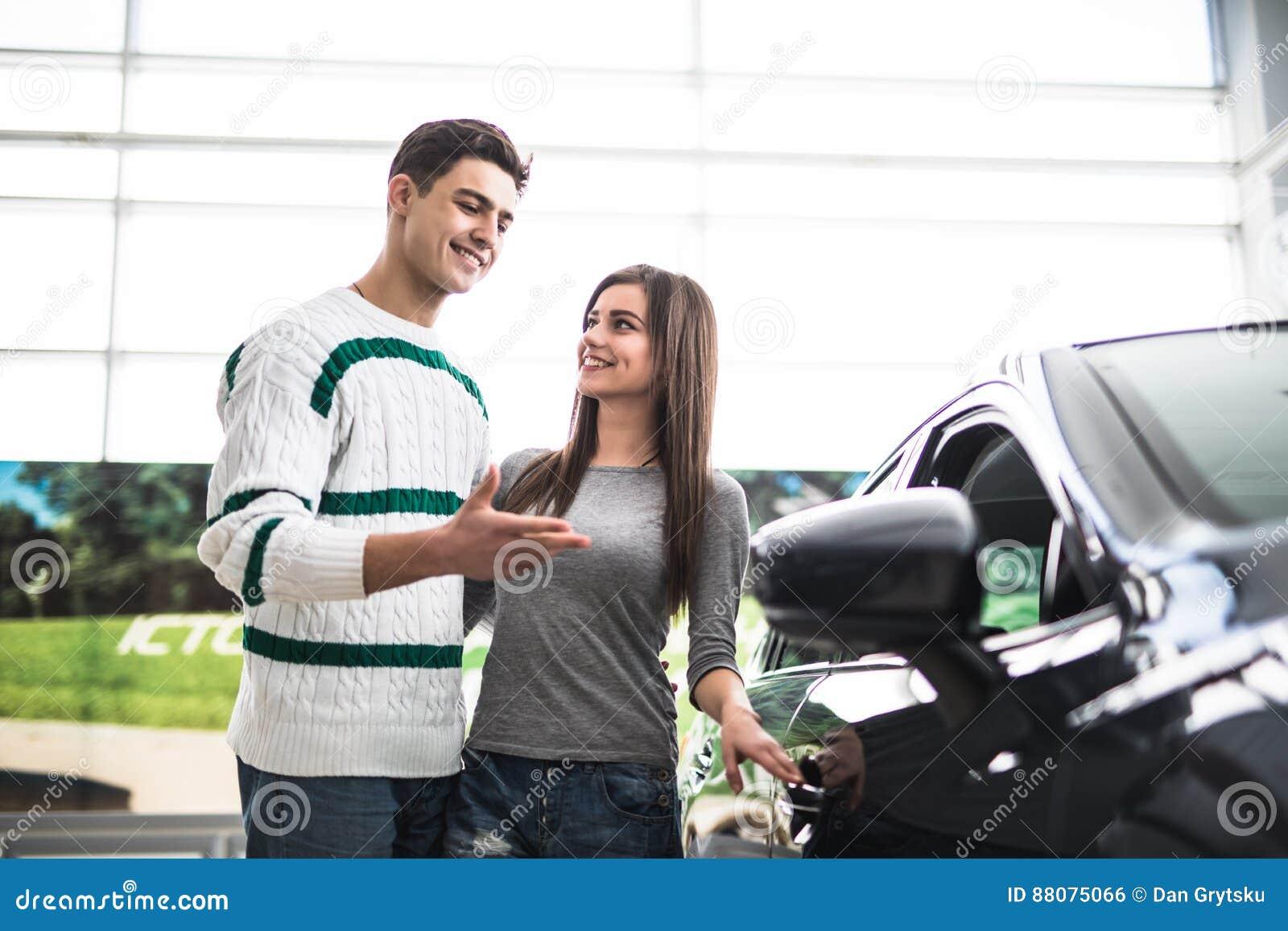 Pares novos bonitos que estão no negócio que escolhe o carro comprar Homem aguçado no carro