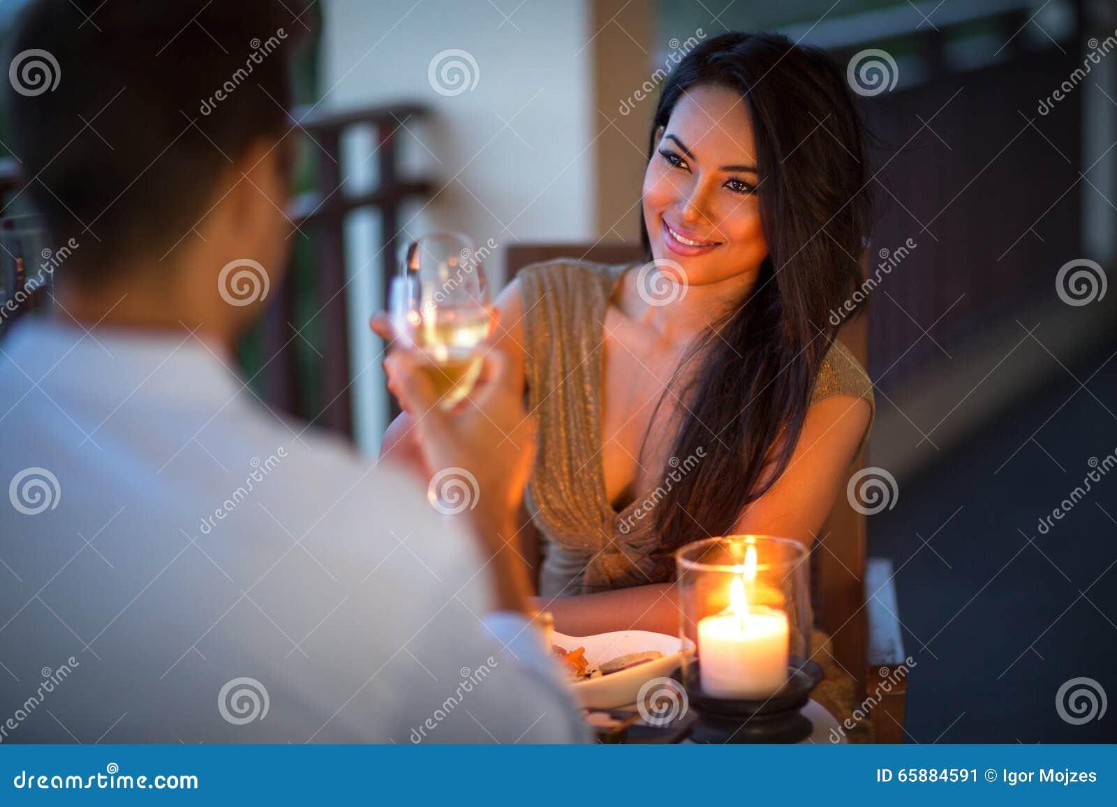 Pares novos com um jantar romântico com velas