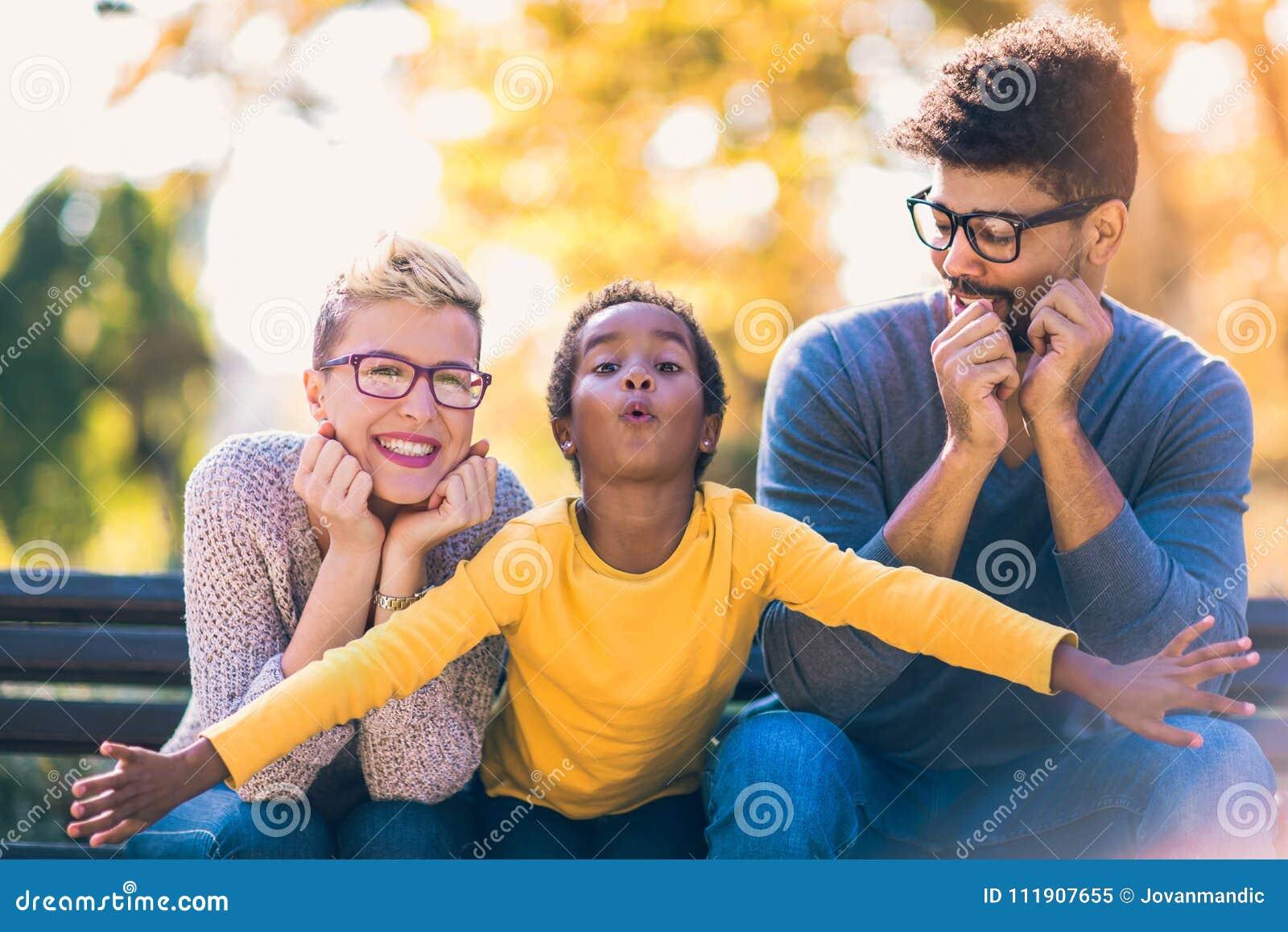 Pares novos da raça misturada que passam o tempo com sua filha