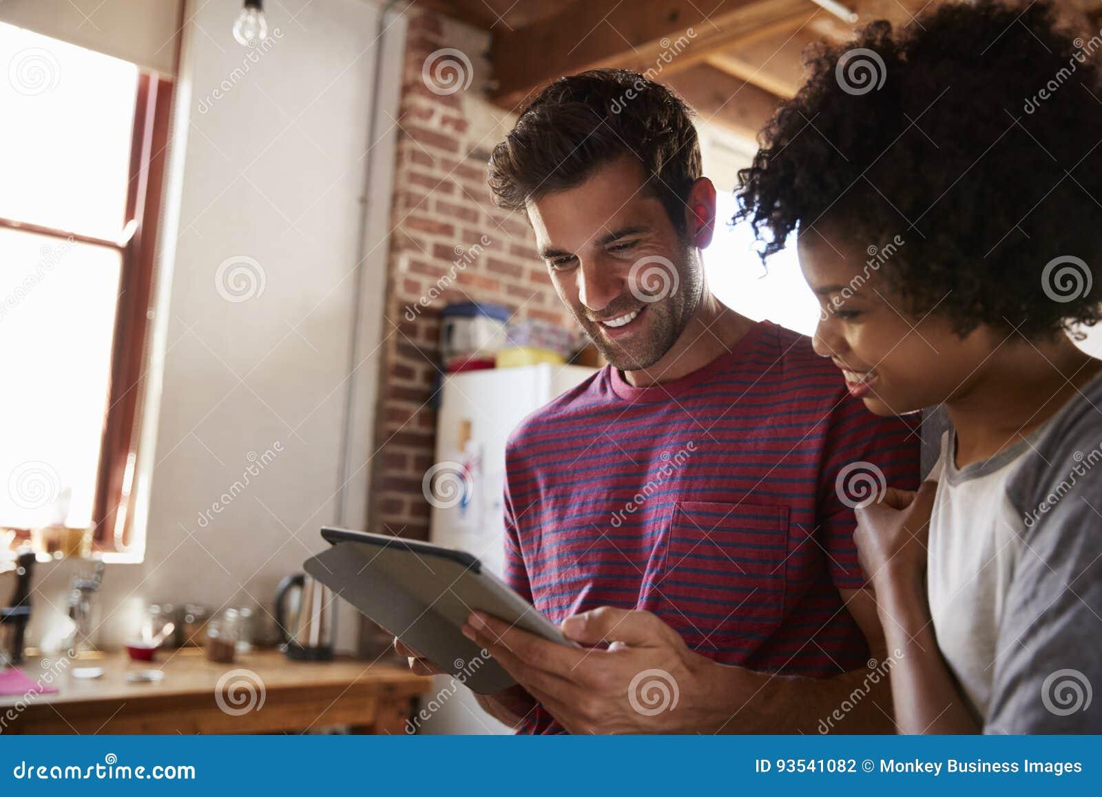 Pares novos da raça misturada usando a tabuleta na cozinha, fim acima