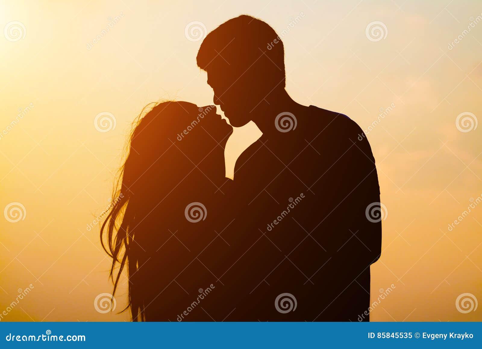 Pares novos da silhueta que beijam sobre o fundo do por do sol