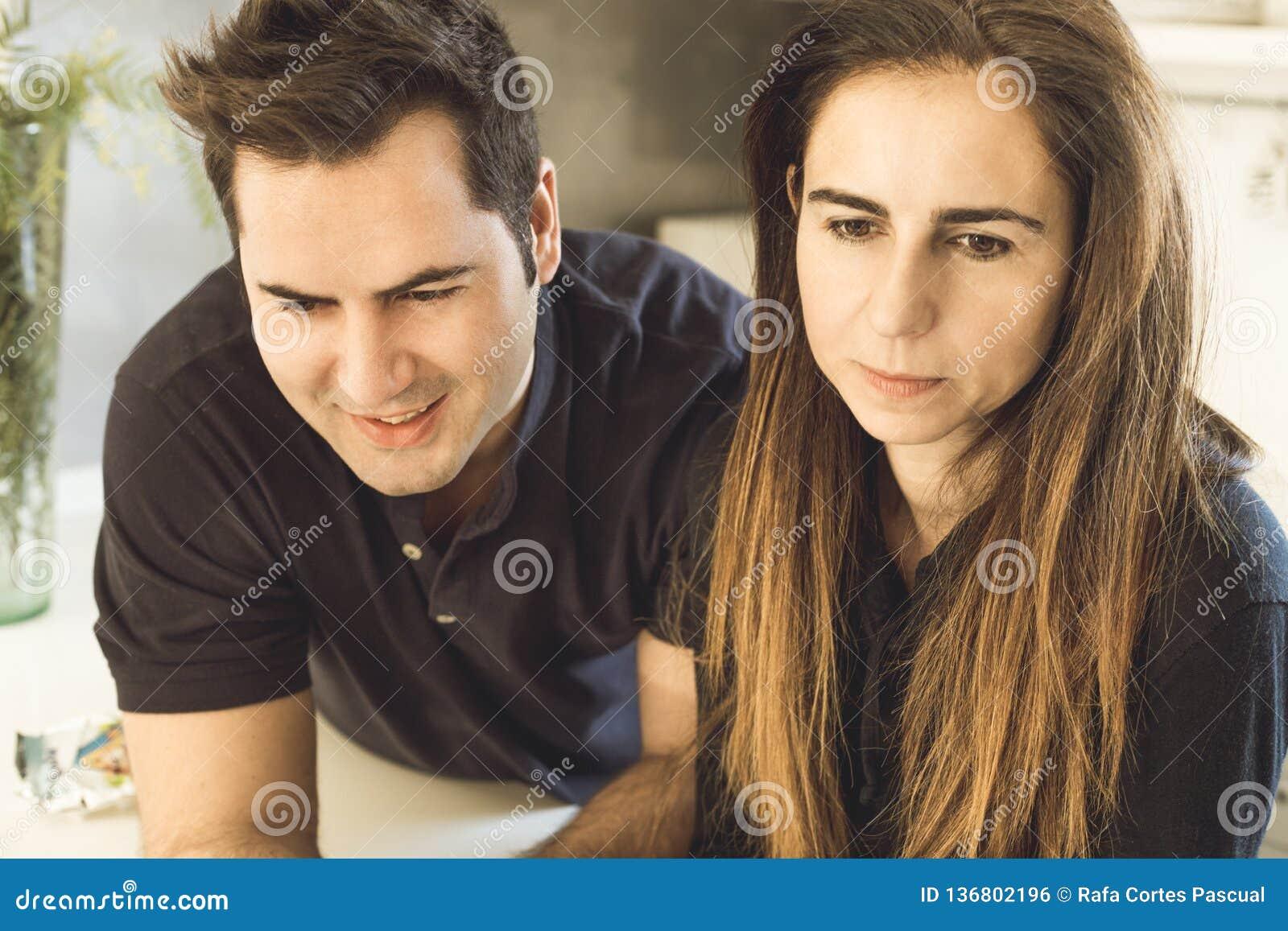 Pares novos de amantes que beijam e que abraçam na cozinha Homem e mulher que mostram a afeição e a ternura