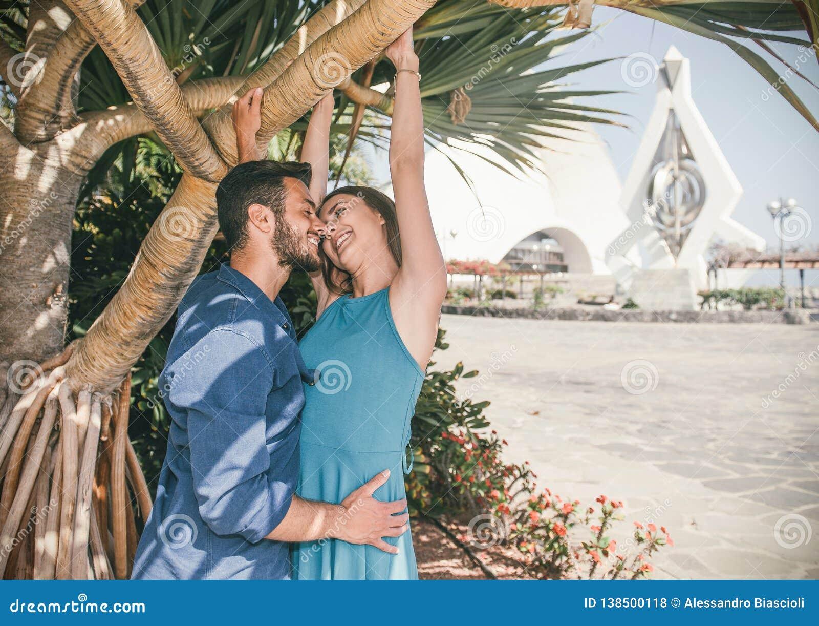 Pares novos de amor perto do beijo exterior - amantes felizes românticos que têm uma história bonito do amor nas férias em sua lu