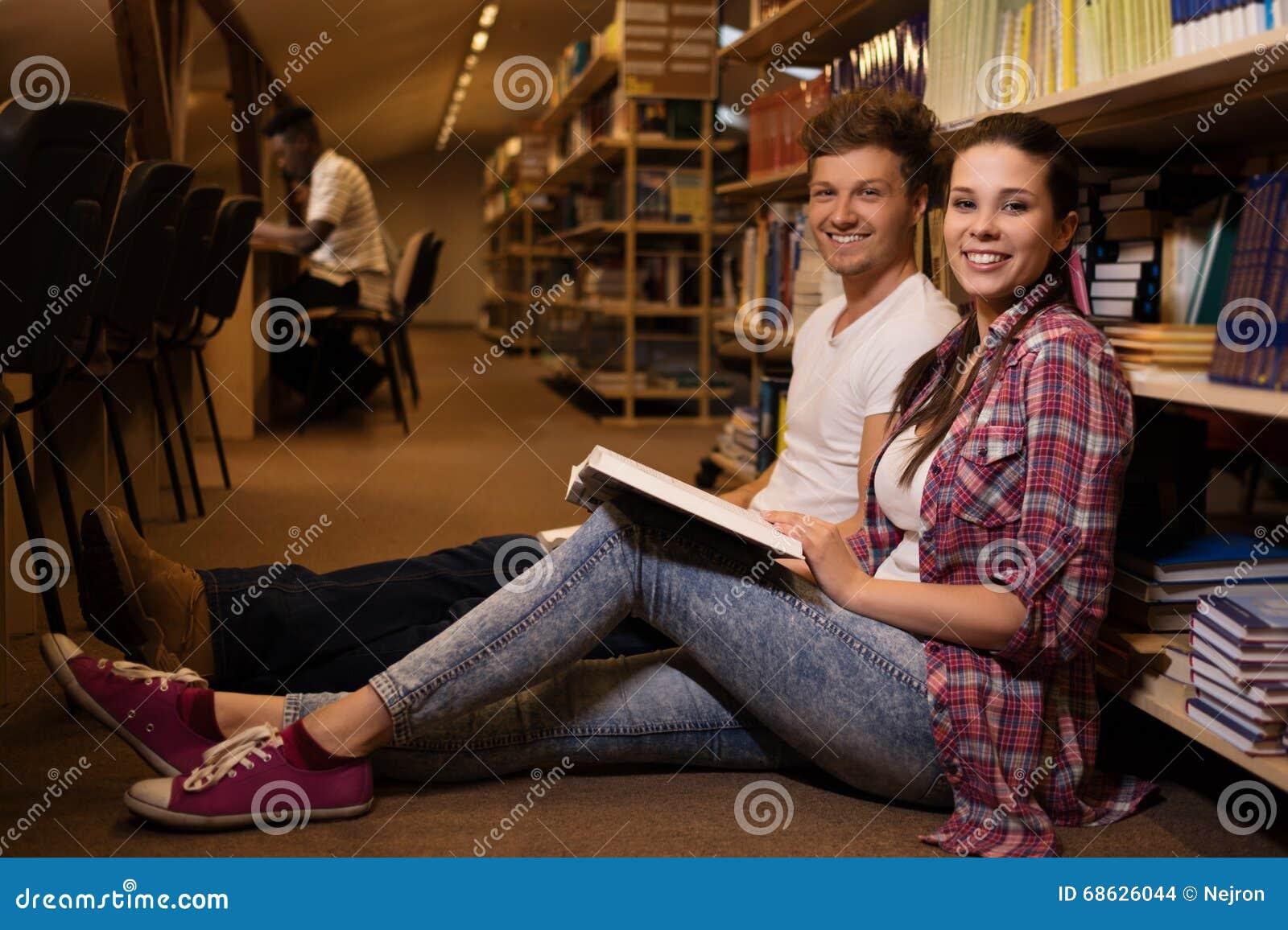 Pares novos de estudantes alegres que sentam-se no assoalho e que estudam na biblioteca da universidade