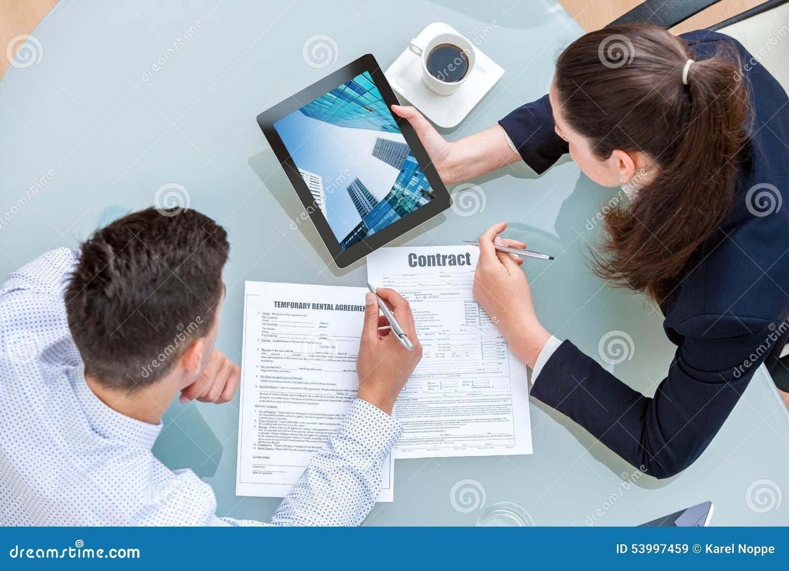 Pares novos do negócio que discutem o acordo alugado