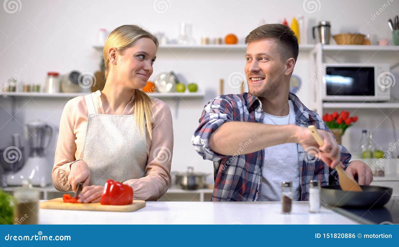 Pares novos do vegetariano que cozinham vegetais, nutrição saudável, tempo feliz junto