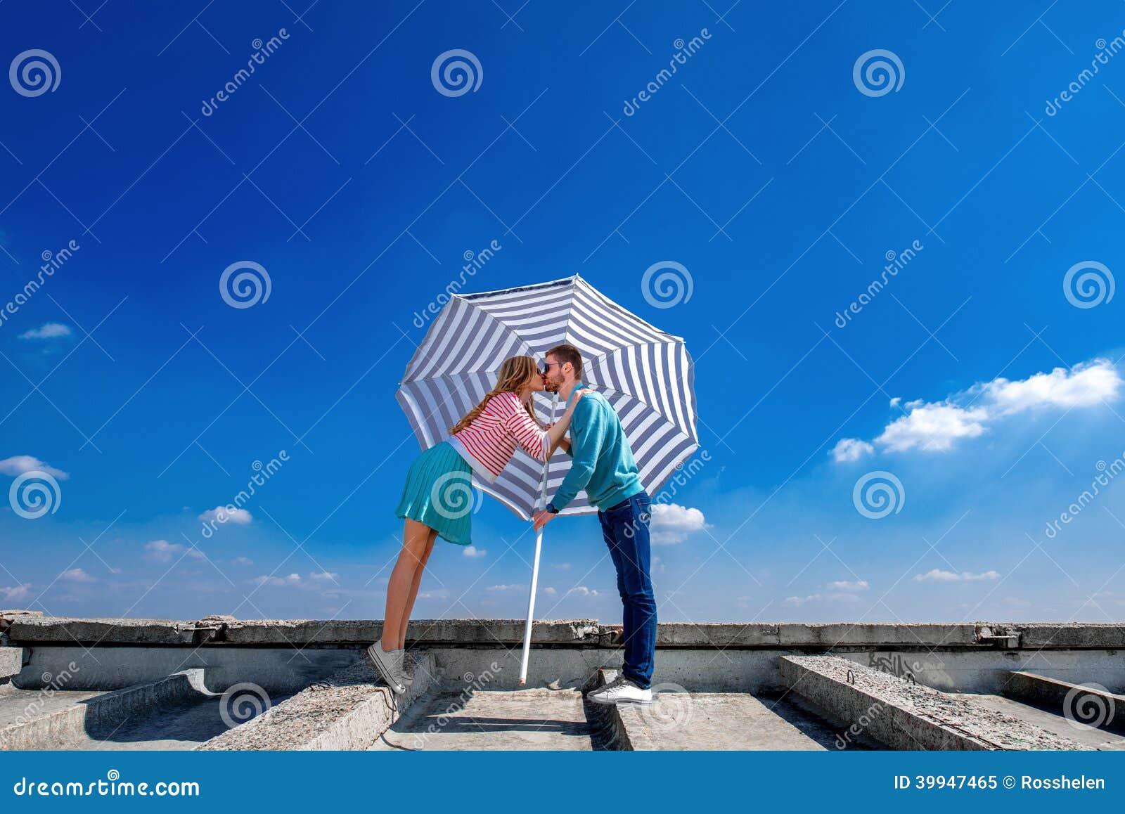 Pares novos e bonitos que beijam no telhado sob o guarda-chuva o