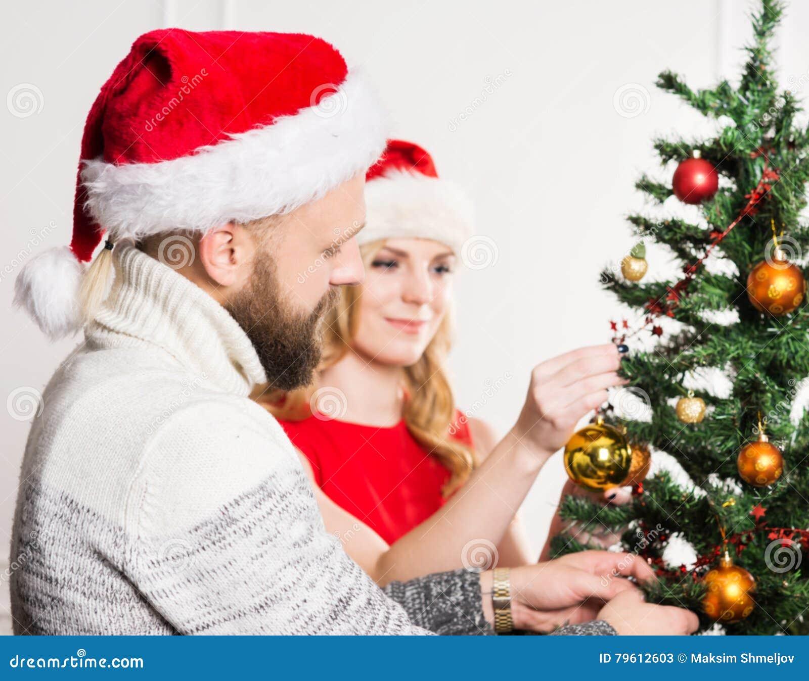 Pares novos em chapéus do Natal ao lado de uma árvore de Natal