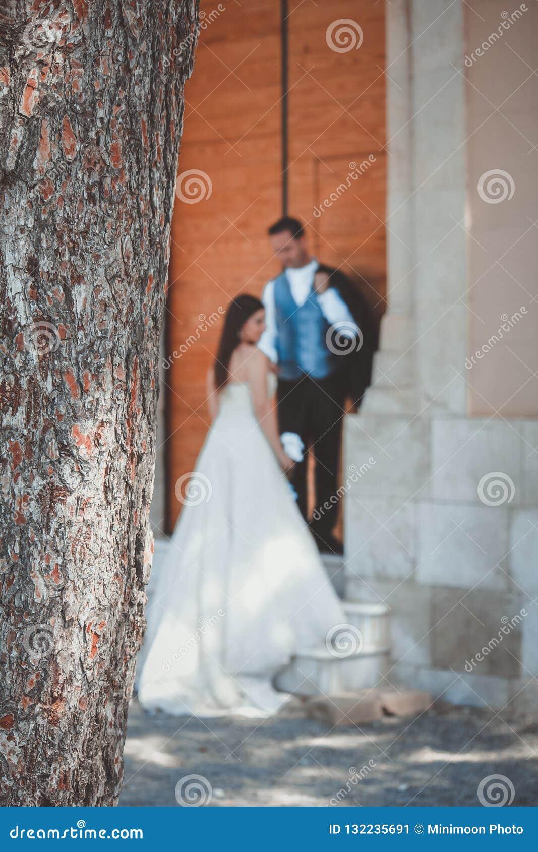 Pares novos em seu dia do casamento, em uma grande escadaria