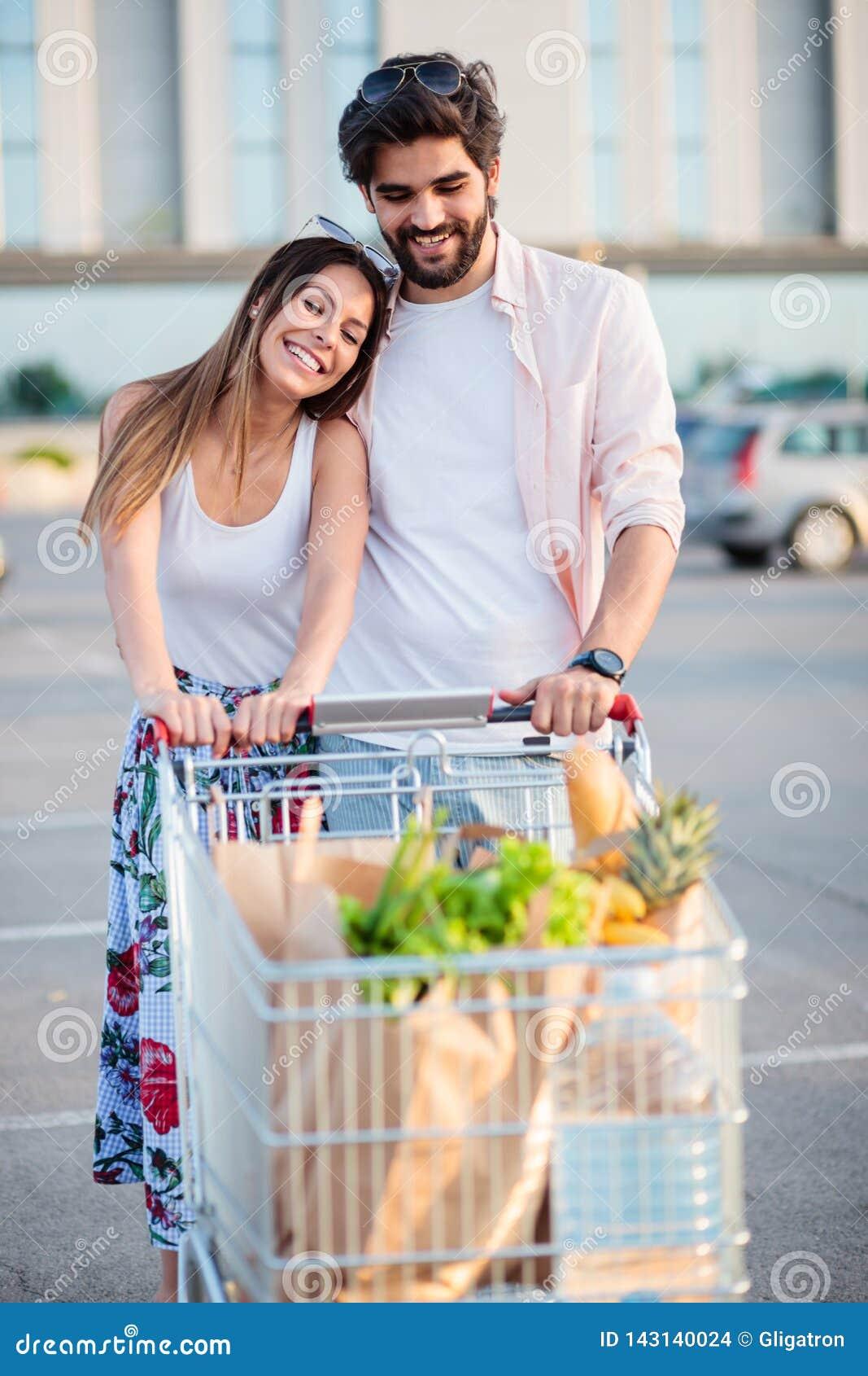 Pares novos felizes com o carrinho de compras completo na frente da alameda