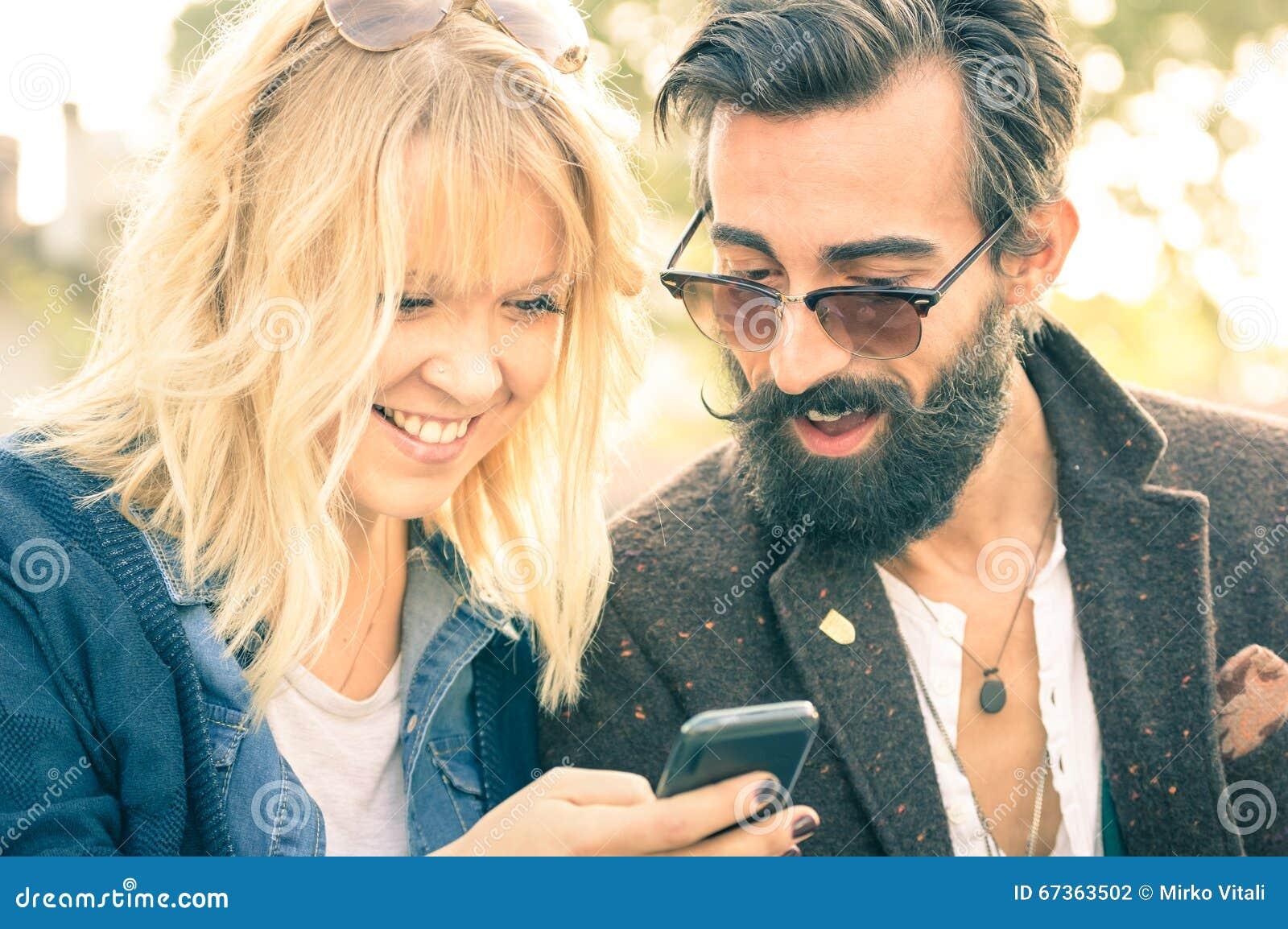 Pares novos felizes com a roupa do vintage que tem o divertimento com telefone