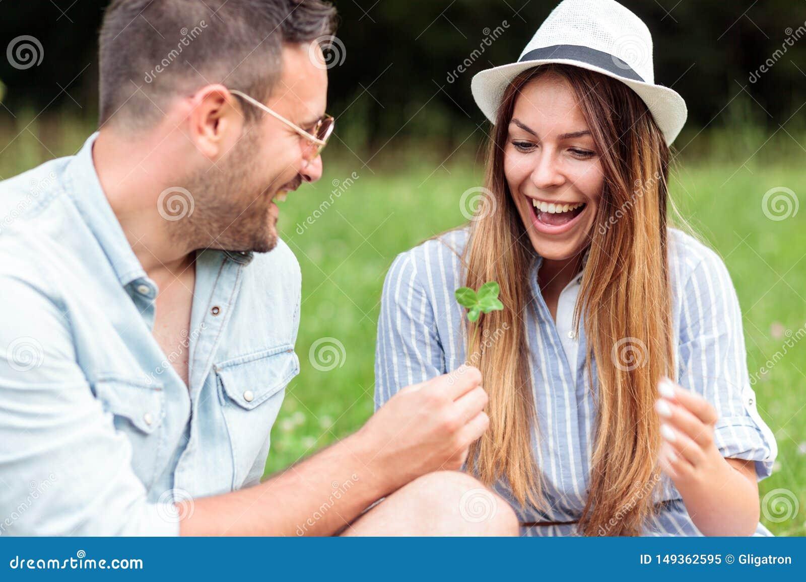 Pares novos felizes de sorriso que passam o tempo junto em um piquenique no parque