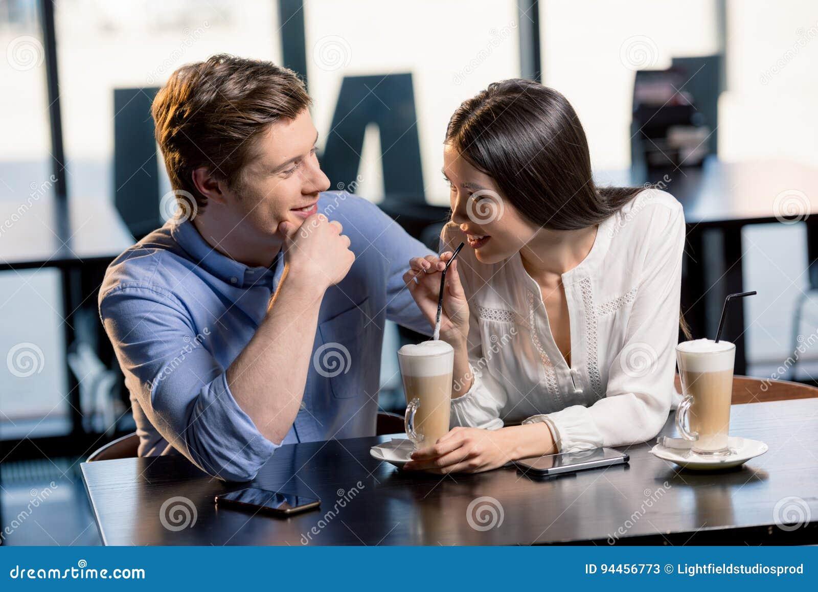 Pares novos felizes no amor na data romântica no restaurante