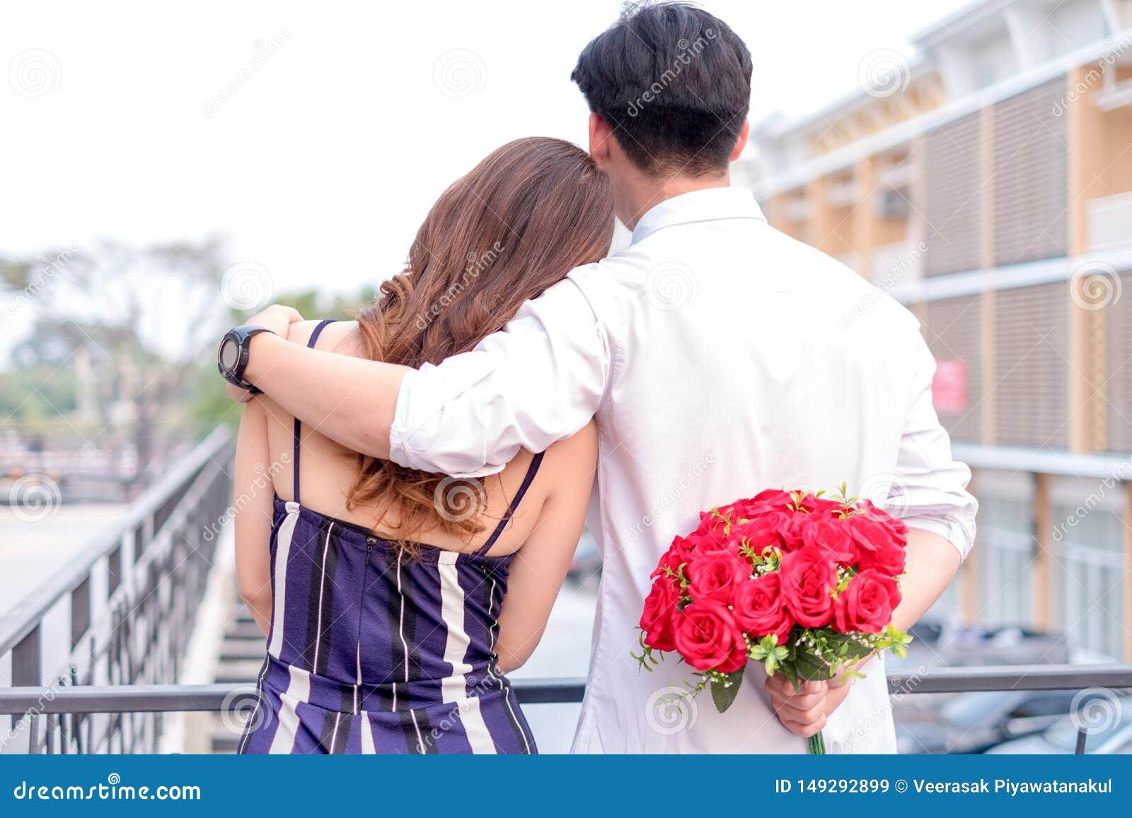 Pares novos felizes no amor que abraça e que guarda rosas vermelhas nas mãos para a surpresa sua amiga, conceito dos pares, a Din