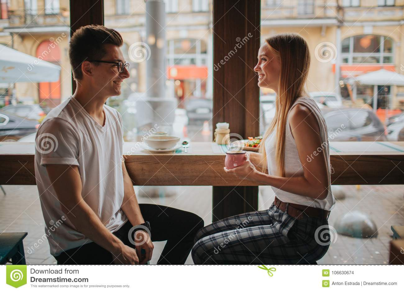Pares novos felizes no amor que tem uma data agradável em uma barra ou em um restaurante Eles que dizem algumas histórias sobre s