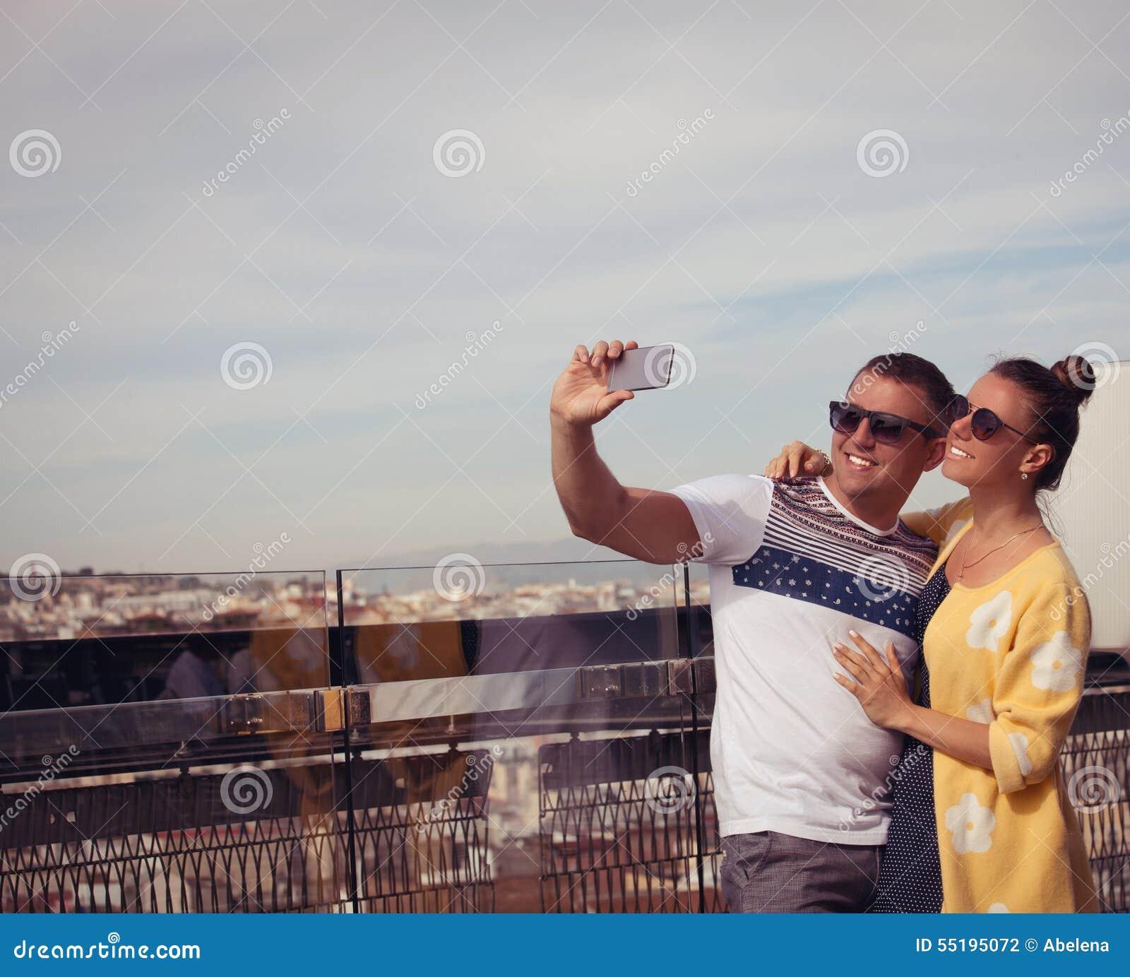 Pares novos felizes no amor que toma a foto do autorretrato do selfie