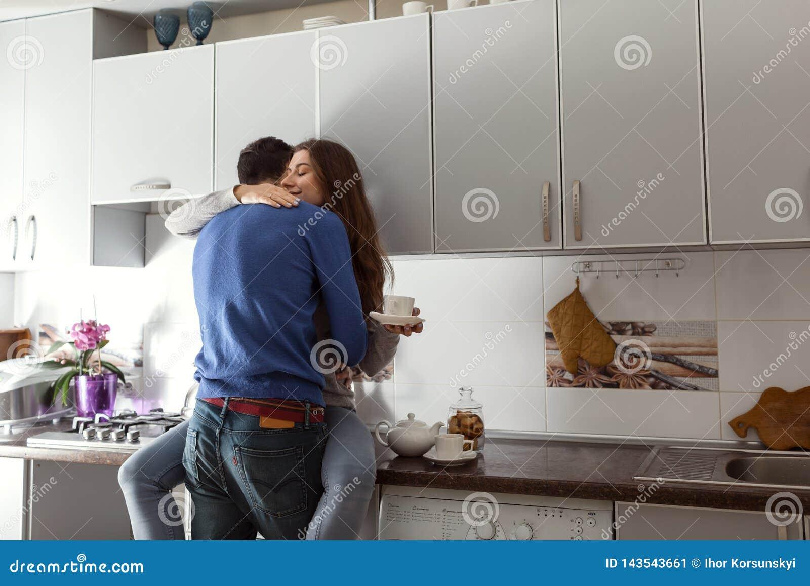 Pares novos felizes que abraçam na cozinha Mulher que senta-se na tabela