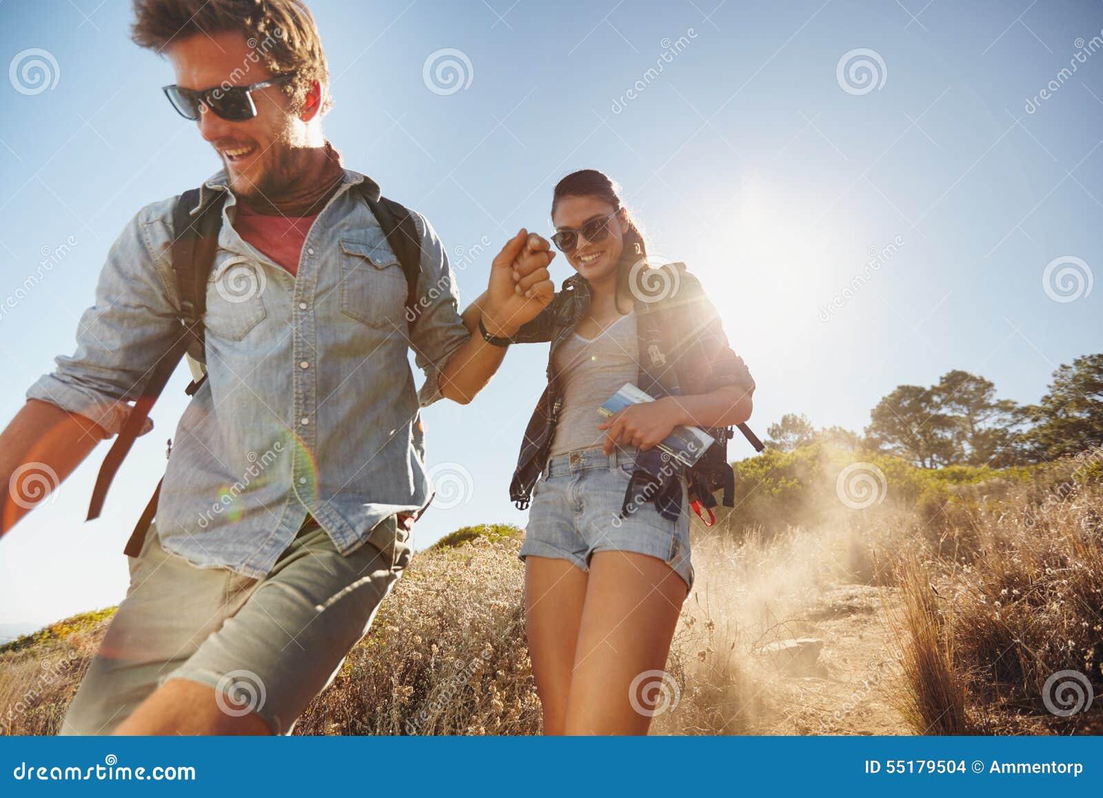 Pares novos felizes que apreciam sua viagem de caminhada