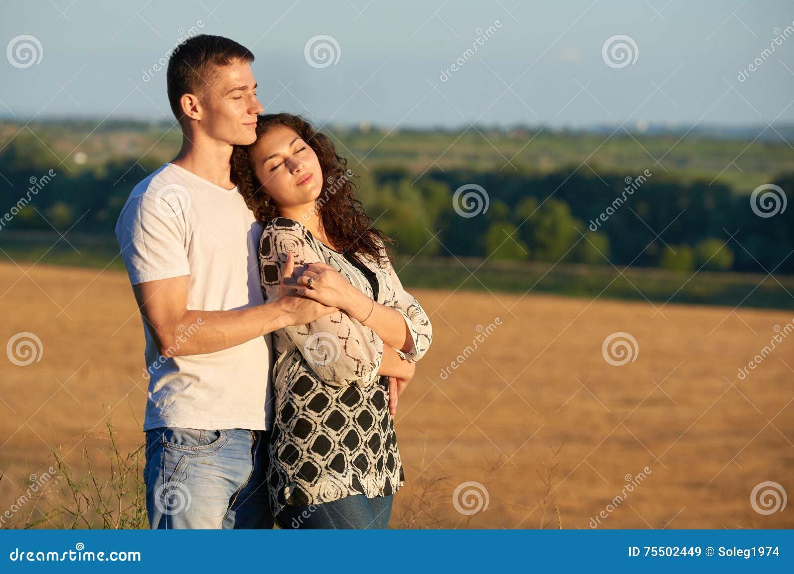 Pares novos felizes que levantam altamente no país exterior, conceito romântico dos povos, temporada de verão
